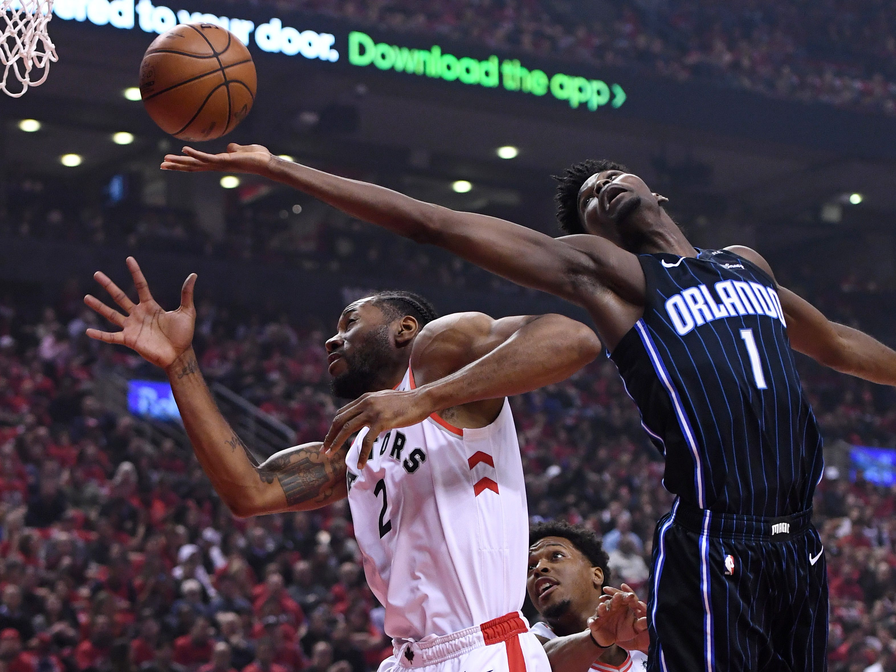 April 23: Orlando Magic forward Jonathan Isaac  (1) reaches for the ball over Toronto Raptors forward Kawhi Leonard (2) during Game 5 at Scotiabank Arena. The Raptors eliminated the Magic with a 115-96 win.