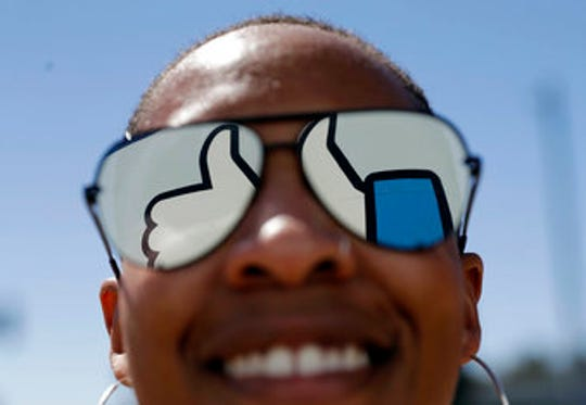 In this March 28, 2018, file photo, a visitor poses for a photo with the Facebook logo reflected on her sunglasses at the company's headquarters in Menlo Park, Calif. Facebook reports earnings Wednesday, April 24, 2019.