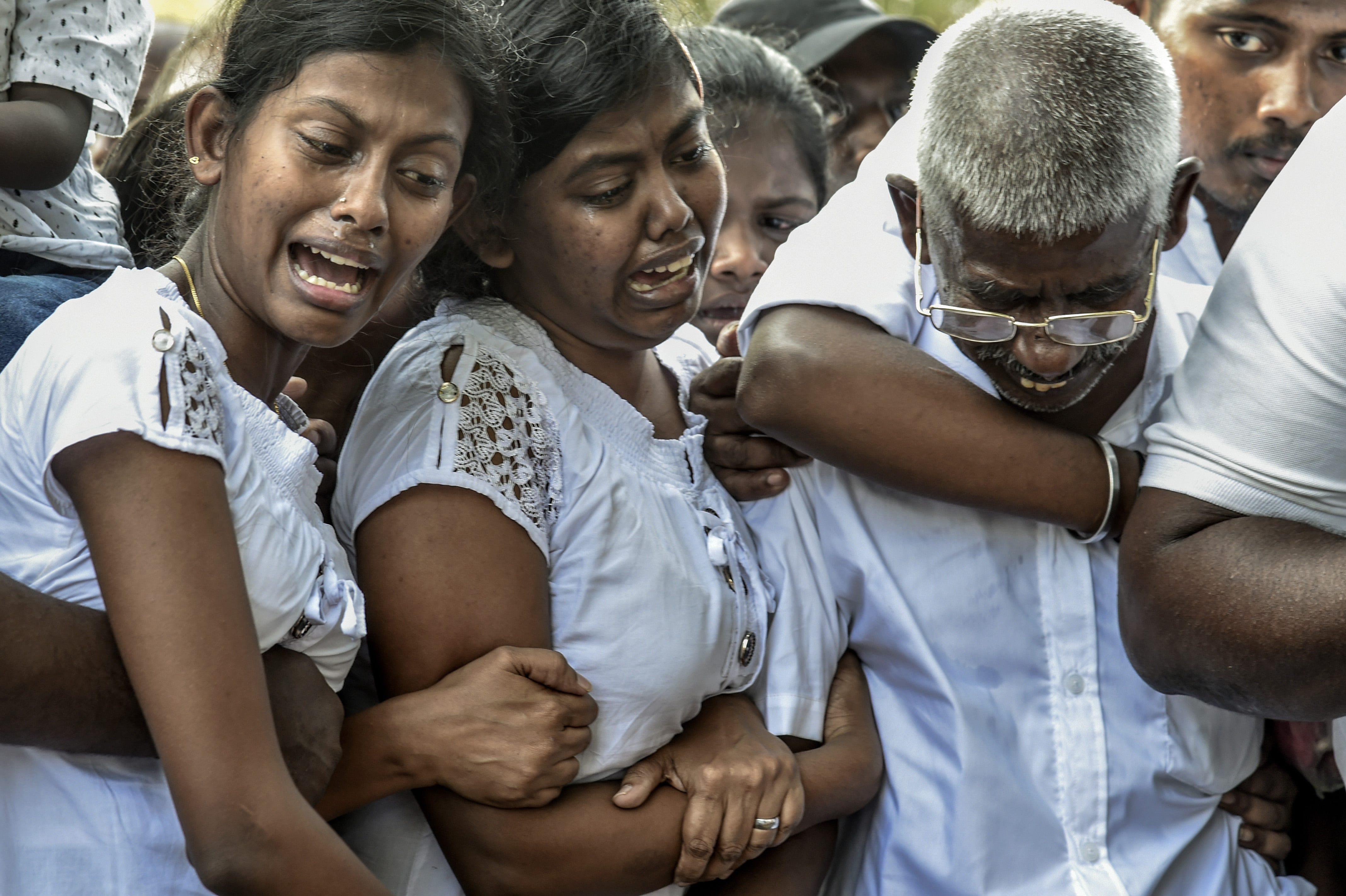 Relatives cry at the graveside during a funeral April 24 for a victim of the Easter Sunday bombings in Colombo, Sri Lanka.