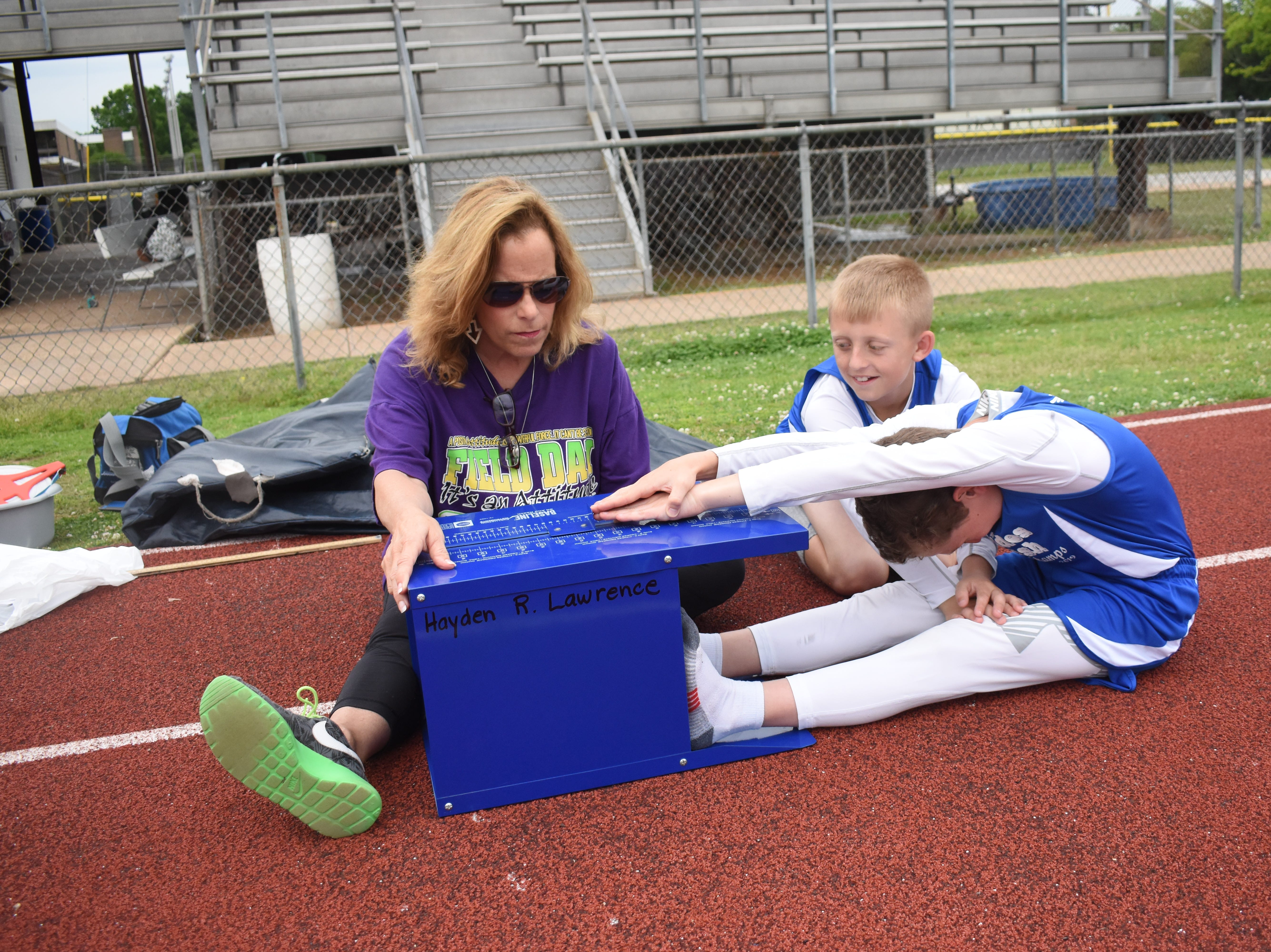 Margaret LaBorde, Rapides Parish Fitness team coach and coordinator (left) watches Jacob Dean (right) perform a sit and reach. Dean and Jaxon Ross, both of Nachman Elementary School, are part the 2019 Rapides Parish Fitness Team. They and four other Rapides Parish elementary school students will compete in the 2019 State Championship Fitness Meet to be held Saturday, April 27, 2019 at Alexandria Senior High School. The meet is part of the Governor's Council on Fitness and Sports. Students from throughout Louisiana will compete in seven events: 50-yard dash, sit and reach, pull-ups,  shuttle run, curl-ups (sit-ups), standing long jump, and the 600-yard run. For the past three years, the Rapides Parish Fitness Team has placed first at the meet. Dean was the highest scoring boy last year and won the title of 2018 Mr. Fitness for the State of Louisiana. The meet will be from 10 a.m. to 2 p.m.