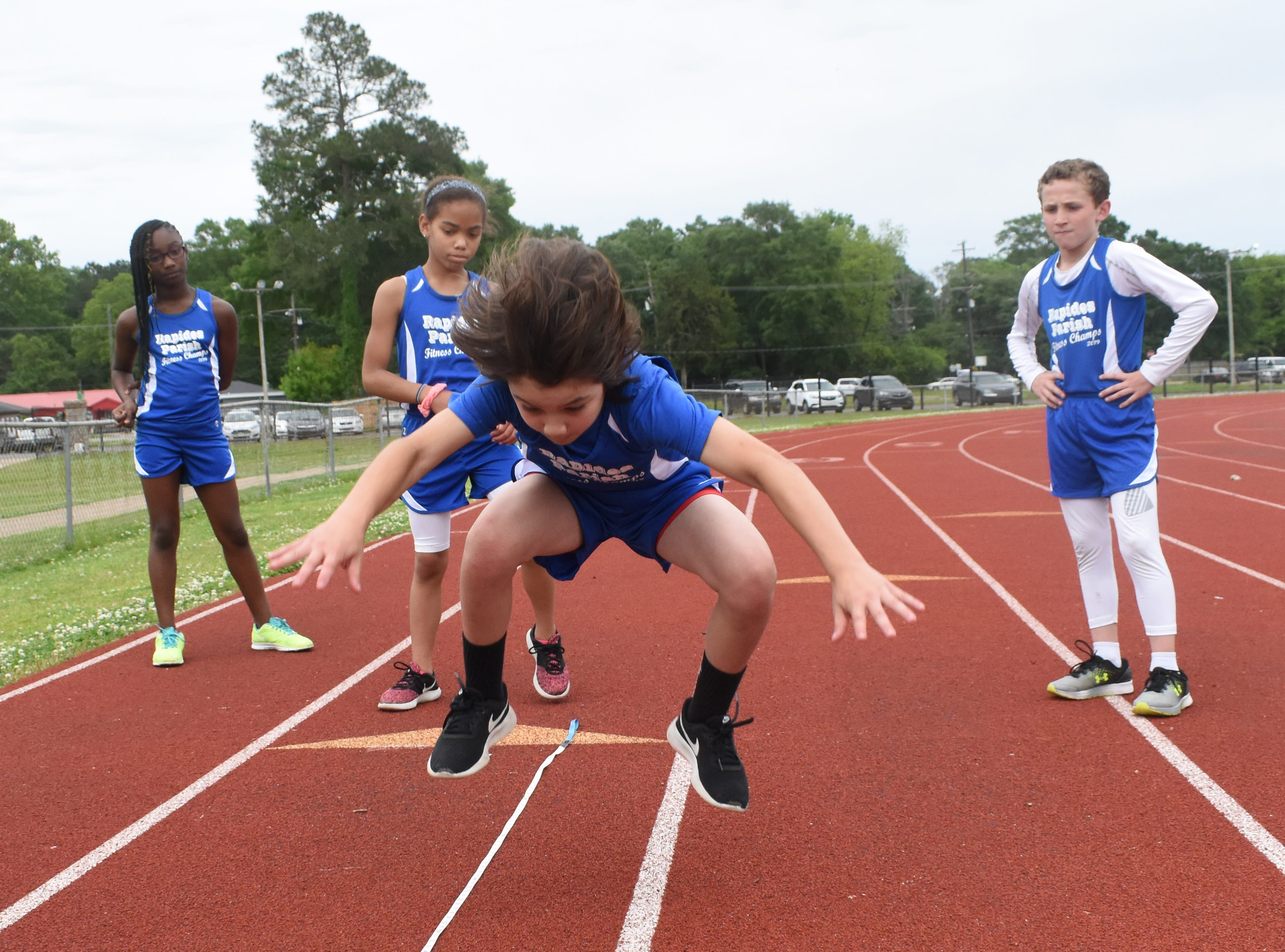 Bryce Warthen (front) of Hayden Lawrence Elementary School, completes a long jump. Bryce is part the 2019 Rapides Parish Fitness Team. He and five other Rapides Parish elementary school students will compete in the 2019 State Championship Fitness Meet to be held Saturday, April 27, 2019 at Alexandria Senior High School. The meet is part of the Governor's Council on Fitness and Sports. Students from throughout Louisiana will compete in seven events: 50-yard dash, sit and reach, pull-ups,  shuttle run, curl-ups (sit-ups), standing long jump, and the 600-yard run. For the past three years, the Rapides Parish Fitness Team has placed first at the meet. Dean was the highest scoring boy last year and won the title of 2018 Mr. Fitness for the State of Louisiana. The meet will be from 10 a.m. to 2 p.m.