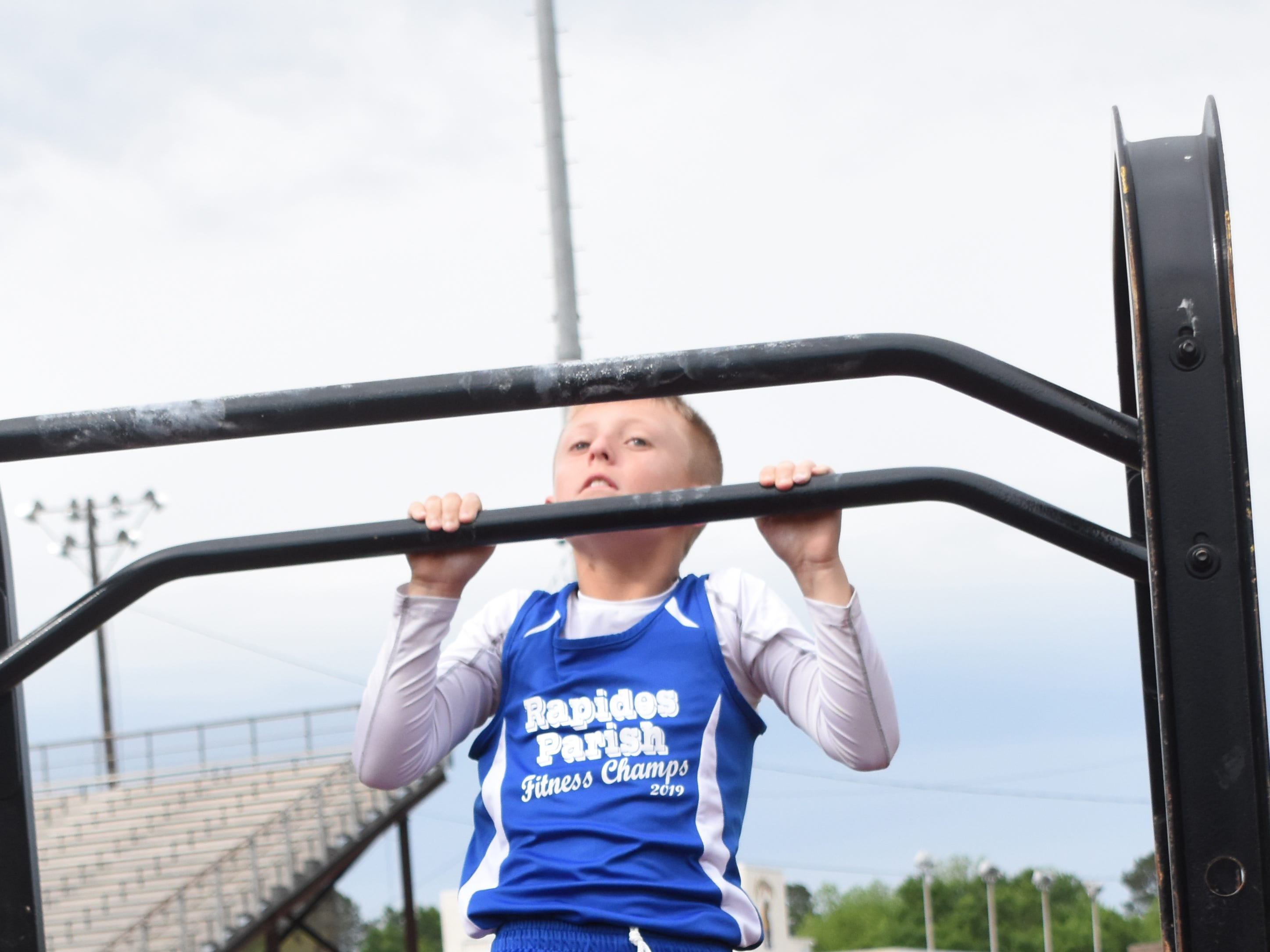Jaxon Ross of Nachman Elementary School does pull-ups. Jaxon is part the 2019 Rapides Parish Fitness Team. Jaxon and five other Rapides Parish elementary school students will compete in the 2019 State Championship Fitness Meet to be held Saturday, April 27, 2019 at Alexandria Senior High School. The meet is part of the Governor's Council on Fitness and Sports. Students from throughout Louisiana will compete in seven events: 50-yard dash, sit and reach, pull-ups,  shuttle run, curl-ups (sit-ups), standing long jump, and the 600-yard run. For the past three years, the Rapides Parish Fitness Team has placed first at the meet. Dean was the highest scoring boy last year and won the title of 2018 Mr. Fitness for the State of Louisiana. The meet will be from 10 a.m. to 2 p.m.
