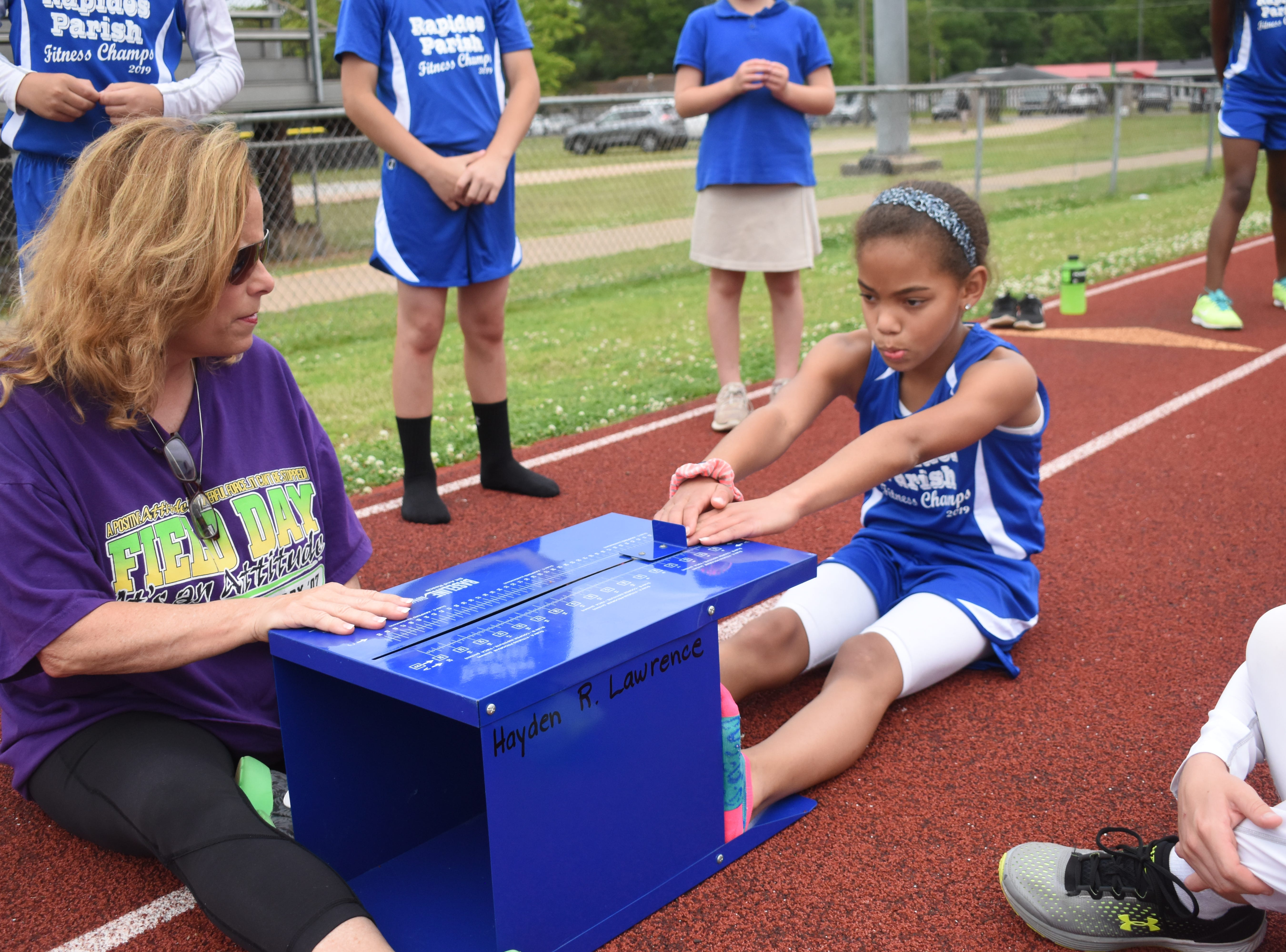 Margaret LaBorde, Rapides Parish Fitness team coach and coordinator (left) watches Madeline Davis of Nachman Elementary School complete a sit and reach. Madeline and other five other Rapides Parish elementary school students will compete in the 2019 State Championship Fitness Meet to be held Saturday, April 27, 2019 at Alexandria Senior High School. The meet is part of the Governor's Council on Fitness and Sports. Students from throughout Louisiana will compete in seven events: 50-yard dash, sit and reach, pull-ups,  shuttle run, curl-ups (sit-ups), standing long jump, and the 600-yard run. For the past three years, the Rapides Parish Fitness Team has placed first at the meet. Dean was the highest scoring boy last year and won the title of 2018 Mr. Fitness for the State of Louisiana. The meet will be from 10 a.m. to 2 p.m.