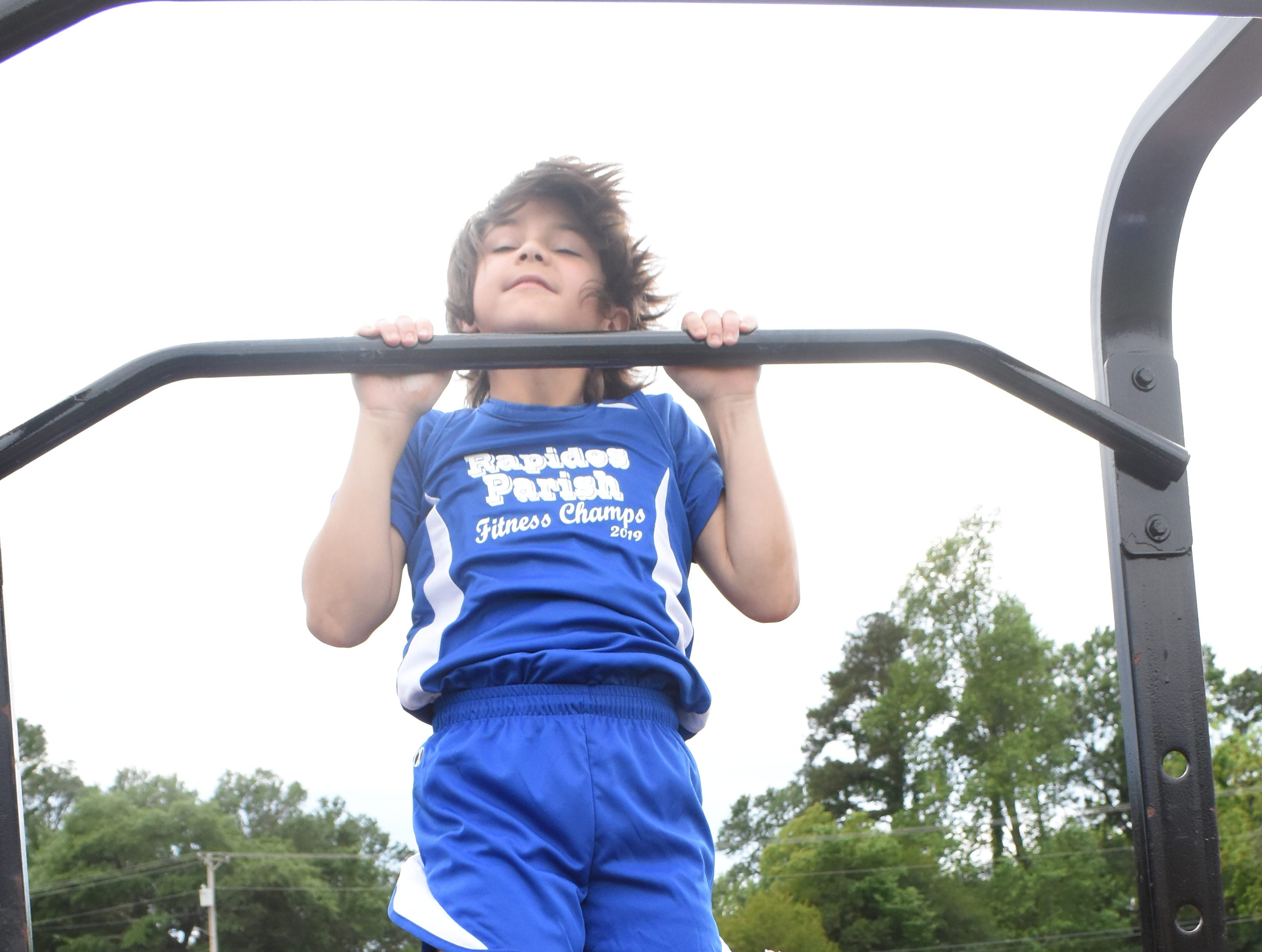 Bryce Warthen of Hayden Lawrence Elementary School, does pull-ups. Bryce is part the 2019 Rapides Parish Fitness Team. He and five other Rapides Parish elementary school students will compete in the 2019 State Championship Fitness Meet to be held Saturday, April 27, 2019 at Alexandria Senior High School. The meet is part of the Governor's Council on Fitness and Sports. Students from throughout Louisiana will compete in seven events: 50-yard dash, sit and reach, pull-ups,  shuttle run, curl-ups (sit-ups), standing long jump, and the 600-yard run. For the past three years, the Rapides Parish Fitness Team has placed first at the meet. Dean was the highest scoring boy last year and won the title of 2018 Mr. Fitness for the State of Louisiana. The meet will be from 10 a.m. to 2 p.m.