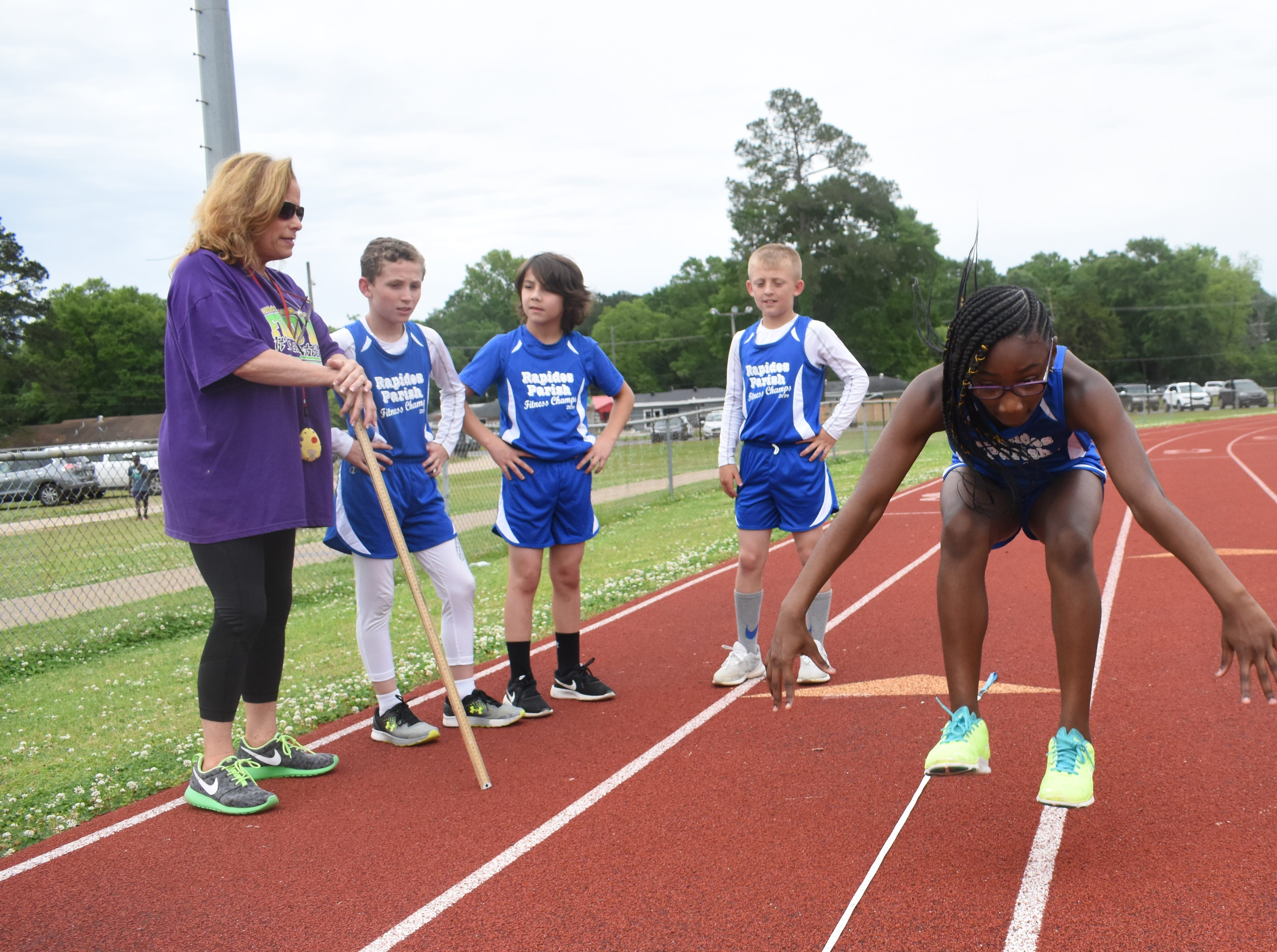 Margaret LaBorde, Rapides Parish Fitness team coach and coordinator (left) watches Amari Dupar of Cherokee Elementary School complete a long jump. Amari and five other Rapides Parish elementary school students will compete in the 2019 State Championship Fitness Meet to be held Saturday, April 27, 2019 at Alexandria Senior High School. The meet is part of the Governor's Council on Fitness and Sports. Students from throughout Louisiana will compete in seven events: 50-yard dash, sit and reach, pull-ups,  shuttle run, curl-ups (sit-ups), standing long jump, and the 600-yard run. For the past three years, the Rapides Parish Fitness Team has placed first at the meet. Dean was the highest scoring boy last year and won the title of 2018 Mr. Fitness for the State of Louisiana. The meet will be from 10 a.m. to 2 p.m.