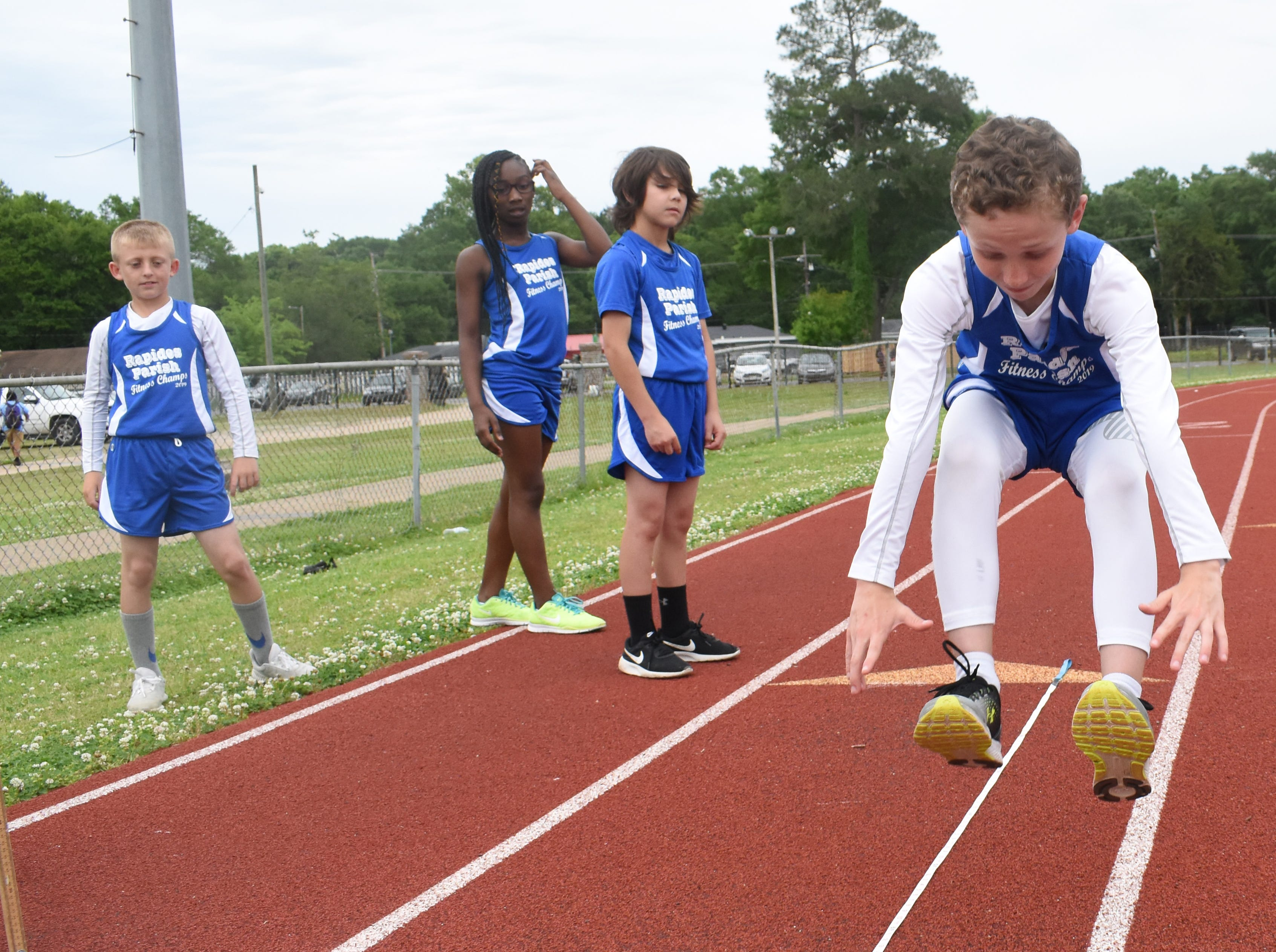 Jacob Dean (left) of Nachman Elementary School complete a long jump. Jacob is part the 2019 Rapides Parish Fitness Team. Jacob and five other Rapides Parish elementary school students will compete in the 2019 State Championship Fitness Meet to be held Saturday, April 27, 2019 at Alexandria Senior High School. The meet is part of the Governor's Council on Fitness and Sports. Students from throughout Louisiana will compete in seven events: 50-yard dash, sit and reach, pull-ups,  shuttle run, curl-ups (sit-ups), standing long jump, and the 600-yard run. For the past three years, the Rapides Parish Fitness Team has placed first at the meet. Dean was the highest scoring boy last year and won the title of 2018 Mr. Fitness for the State of Louisiana. The meet will be from 10 a.m. to 2 p.m.