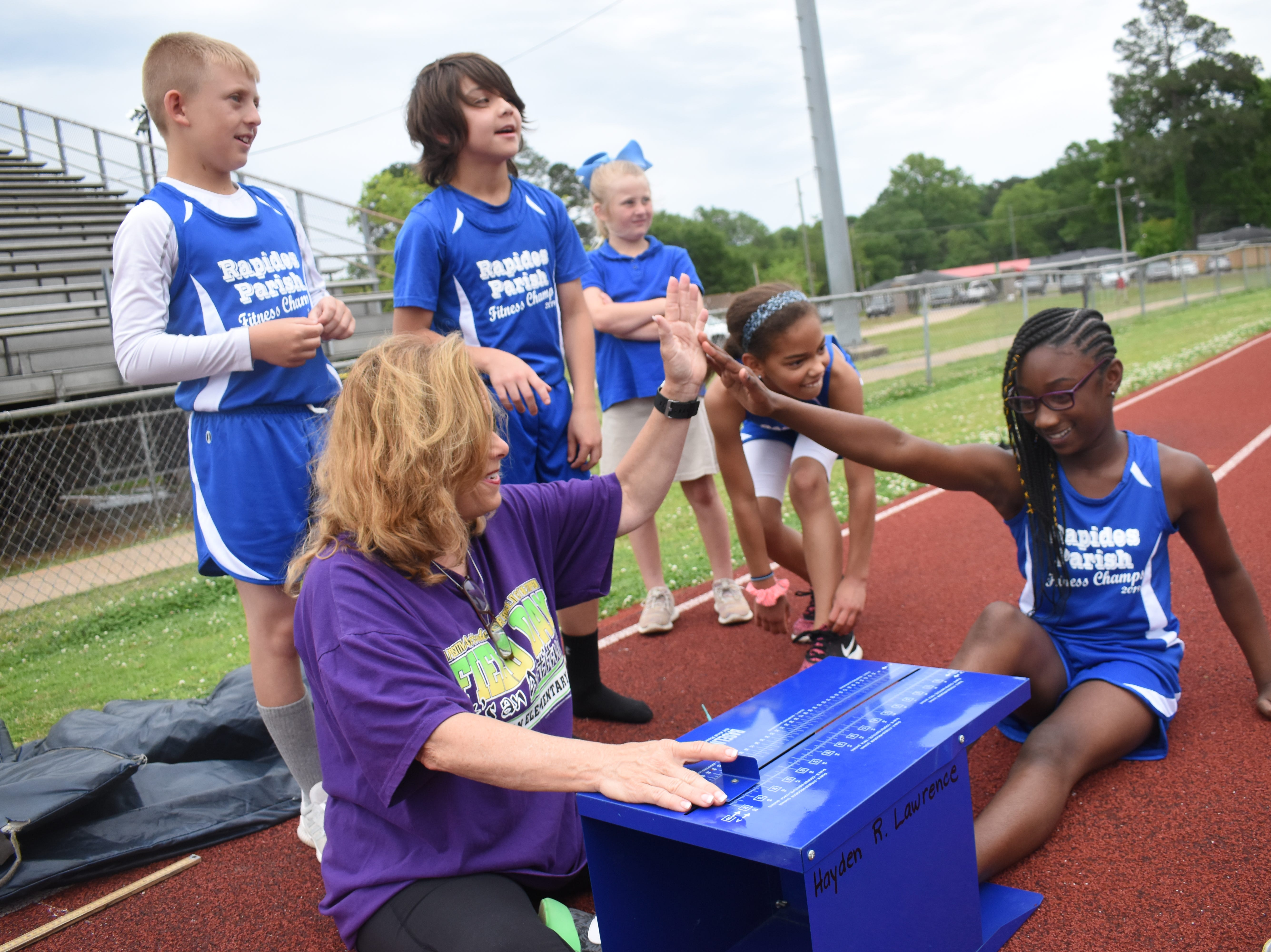 Margaret LaBorde, Rapides Parish Fitness team coach and coordinator (left) congratulates Amari Dupar of Cherokee Elementary School after she completed a sit and reach. Amari and other five other Rapides Parish elementary school students will compete in the 2019 State Championship Fitness Meet to be held Saturday, April 27, 2019 at Alexandria Senior High School. The meet is part of the Governor's Council on Fitness and Sports. Students from throughout Louisiana will compete in seven events: 50-yard dash, sit and reach, pull-ups,  shuttle run, curl-ups (sit-ups), standing long jump, and the 600-yard run. For the past three years, the Rapides Parish Fitness Team has placed first at the meet. Dean was the highest scoring boy last year and won the title of 2018 Mr. Fitness for the State of Louisiana. The meet will be from 10 a.m. to 2 p.m.