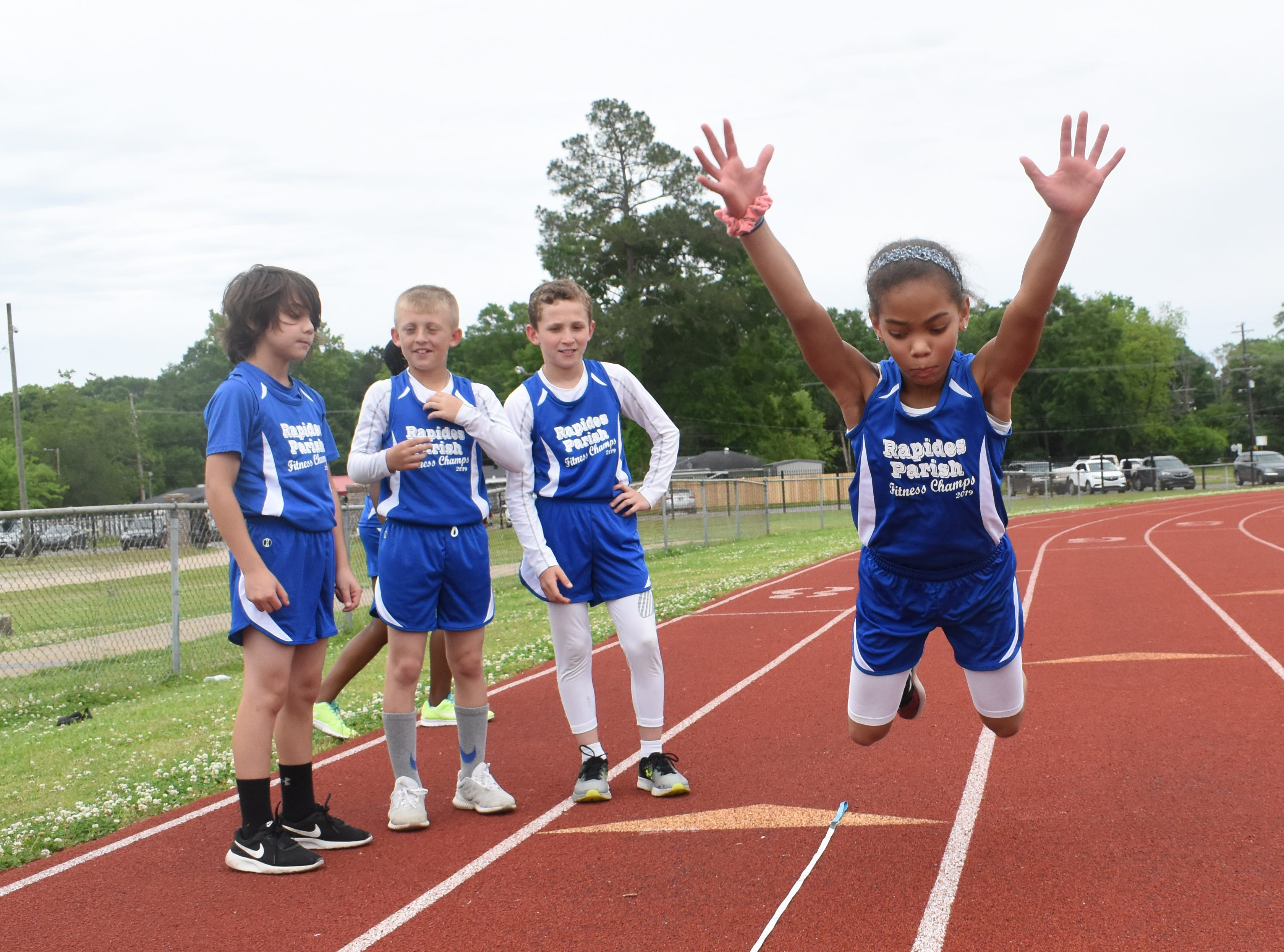 Madeline Davis (left) of Nachman Elementary School complete a long jump. Madeline is part the 2019 Rapides Parish Fitness Team. Madeline and five other Rapides Parish elementary school students will compete in the 2019 State Championship Fitness Meet to be held Saturday, April 27, 2019 at Alexandria Senior High School. The meet is part of the Governor's Council on Fitness and Sports. Students from throughout Louisiana will compete in seven events: 50-yard dash, sit and reach, pull-ups,  shuttle run, curl-ups (sit-ups), standing long jump, and the 600-yard run. For the past three years, the Rapides Parish Fitness Team has placed first at the meet. Dean was the highest scoring boy last year and won the title of 2018 Mr. Fitness for the State of Louisiana. The meet will be from 10 a.m. to 2 p.m.