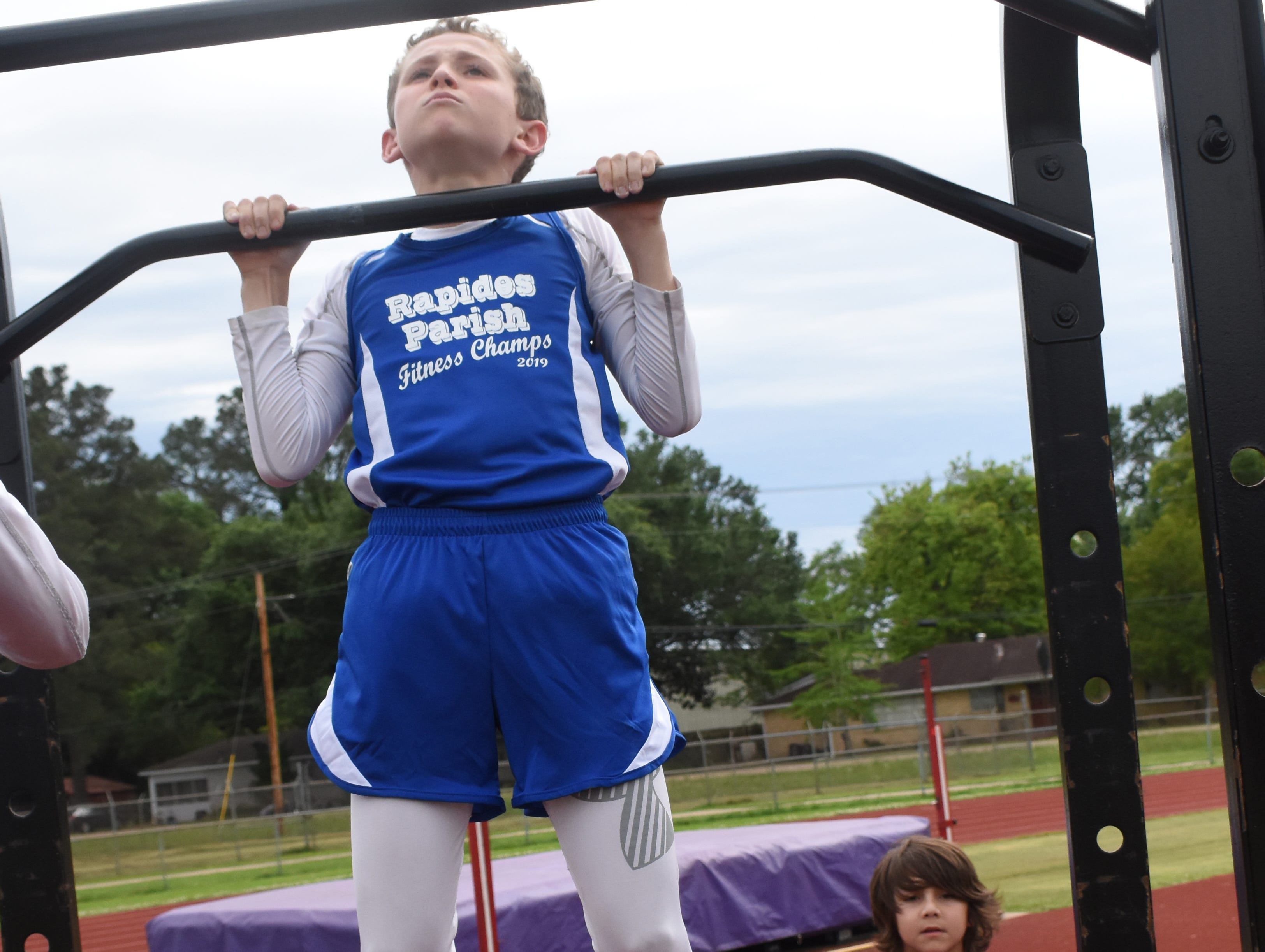 Jacob Dean of Nachman Elementary School does pull-ups. Jacob is part the 2019 Rapides Parish Fitness Team. Jacob and five other Rapides Parish elementary school students will compete in the 2019 State Championship Fitness Meet to be held Saturday, April 27, 2019 at Alexandria Senior High School. The meet is part of the Governor's Council on Fitness and Sports. Students from throughout Louisiana will compete in seven events: 50-yard dash, sit and reach, pull-ups,  shuttle run, curl-ups (sit-ups), standing long jump, and the 600-yard run. For the past three years, the Rapides Parish Fitness Team has placed first at the meet. Dean was the highest scoring boy last year and won the title of 2018 Mr. Fitness for the State of Louisiana. The meet will be from 10 a.m. to 2 p.m.