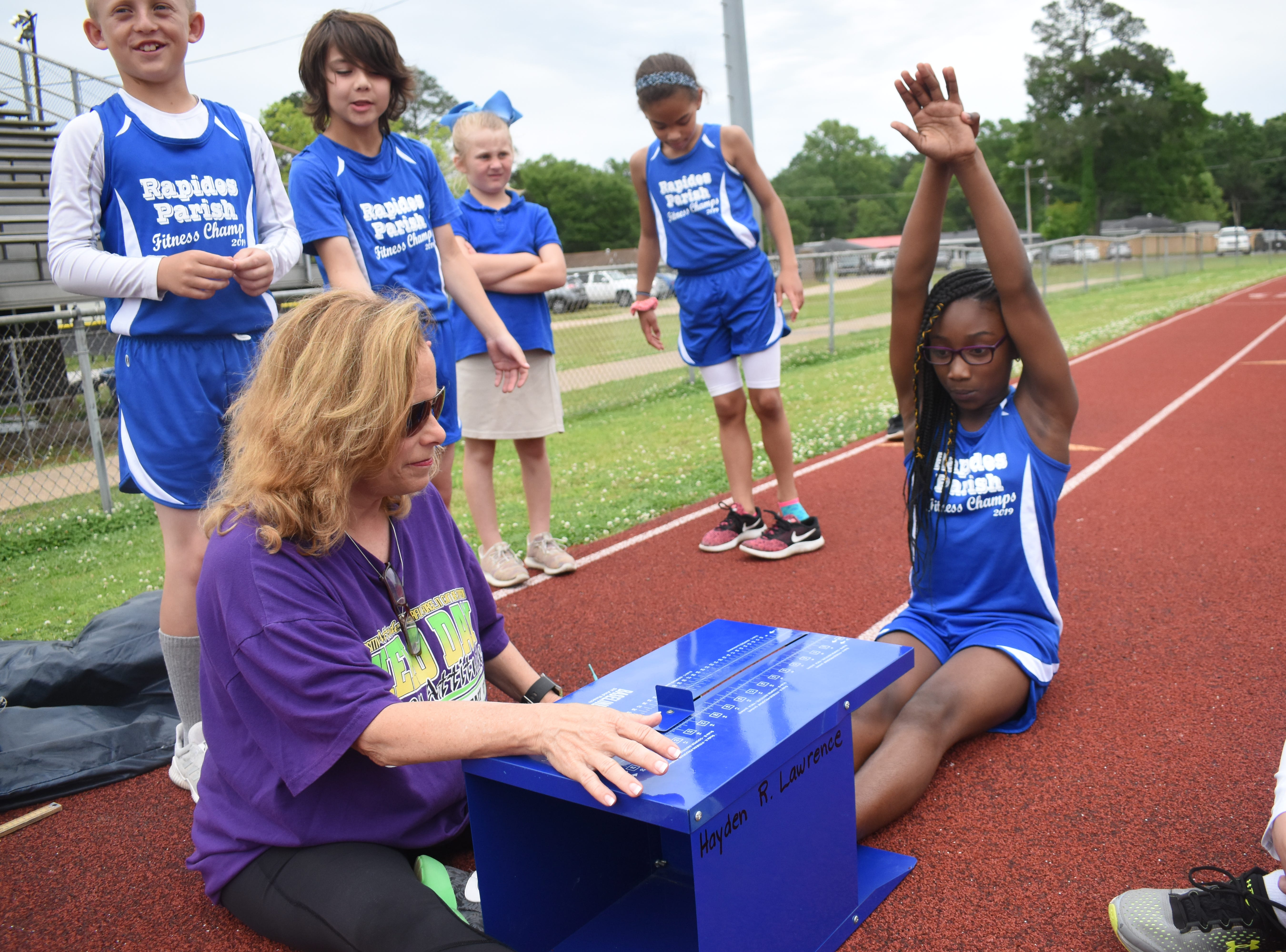 Margaret LaBorde, Rapides Parish Fitness team coach and coordinator (left) watches Amari Dupar of Cherokee Elementary School complete a sit and reach. Amari and other five other Rapides Parish elementary school students will compete in the 2019 State Championship Fitness Meet to be held Saturday, April 27, 2019 at Alexandria Senior High School. The meet is part of the Governor's Council on Fitness and Sports. Students from throughout Louisiana will compete in seven events: 50-yard dash, sit and reach, pull-ups,  shuttle run, curl-ups (sit-ups), standing long jump, and the 600-yard run. For the past three years, the Rapides Parish Fitness Team has placed first at the meet. Dean was the highest scoring boy last year and won the title of 2018 Mr. Fitness for the State of Louisiana. The meet will be from 10 a.m. to 2 p.m.