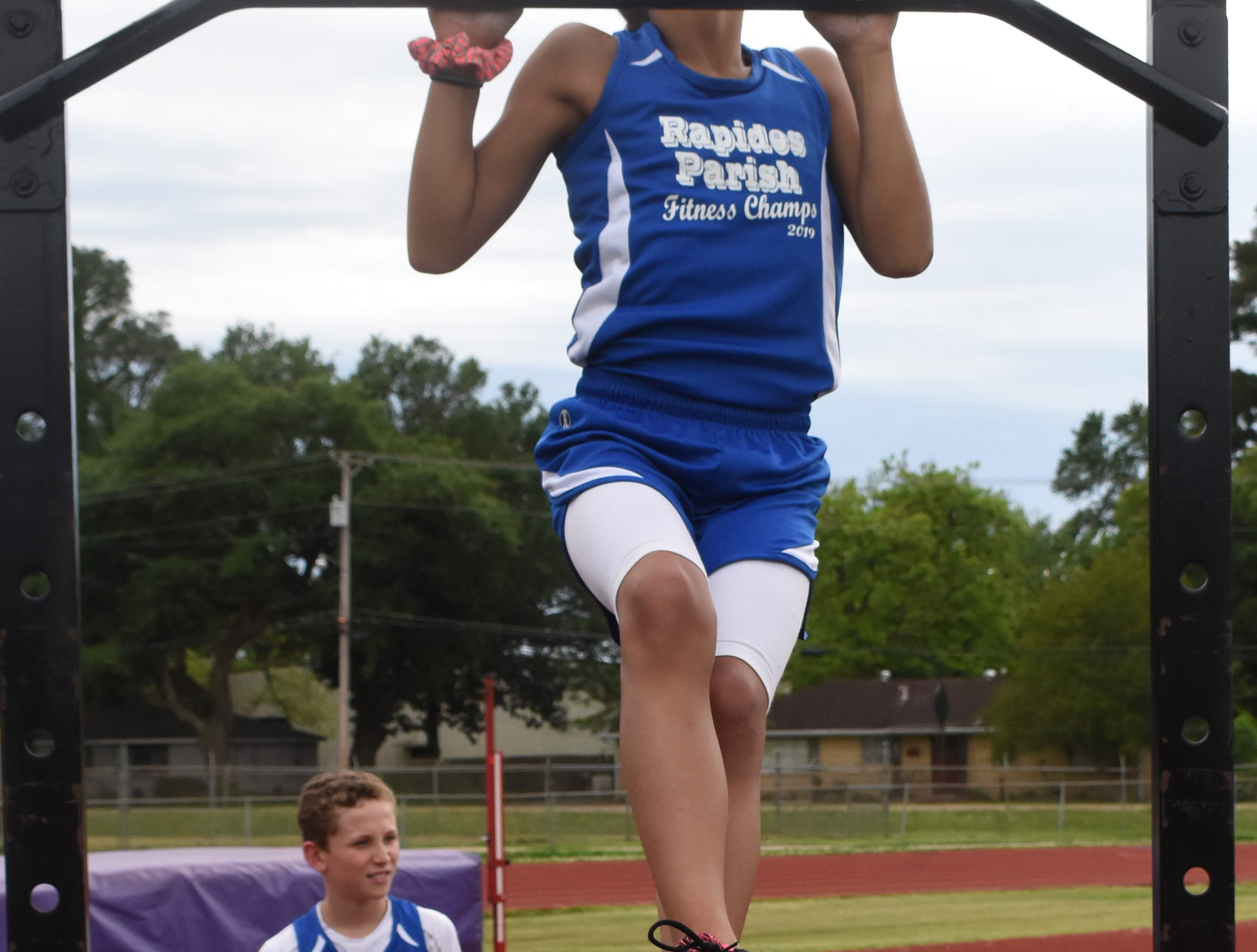 Madeline Davis of Nachman Elementary School does pull-ups. Madeline is part the 2019 Rapides Parish Fitness Team. Madeline and five other Rapides Parish elementary school students will compete in the 2019 State Championship Fitness Meet to be held Saturday, April 27, 2019 at Alexandria Senior High School. The meet is part of the Governor's Council on Fitness and Sports. Students from throughout Louisiana will compete in seven events: 50-yard dash, sit and reach, pull-ups,  shuttle run, curl-ups (sit-ups), standing long jump, and the 600-yard run. For the past three years, the Rapides Parish Fitness Team has placed first at the meet. Dean was the highest scoring boy last year and won the title of 2018 Mr. Fitness for the State of Louisiana. The meet will be from 10 a.m. to 2 p.m.