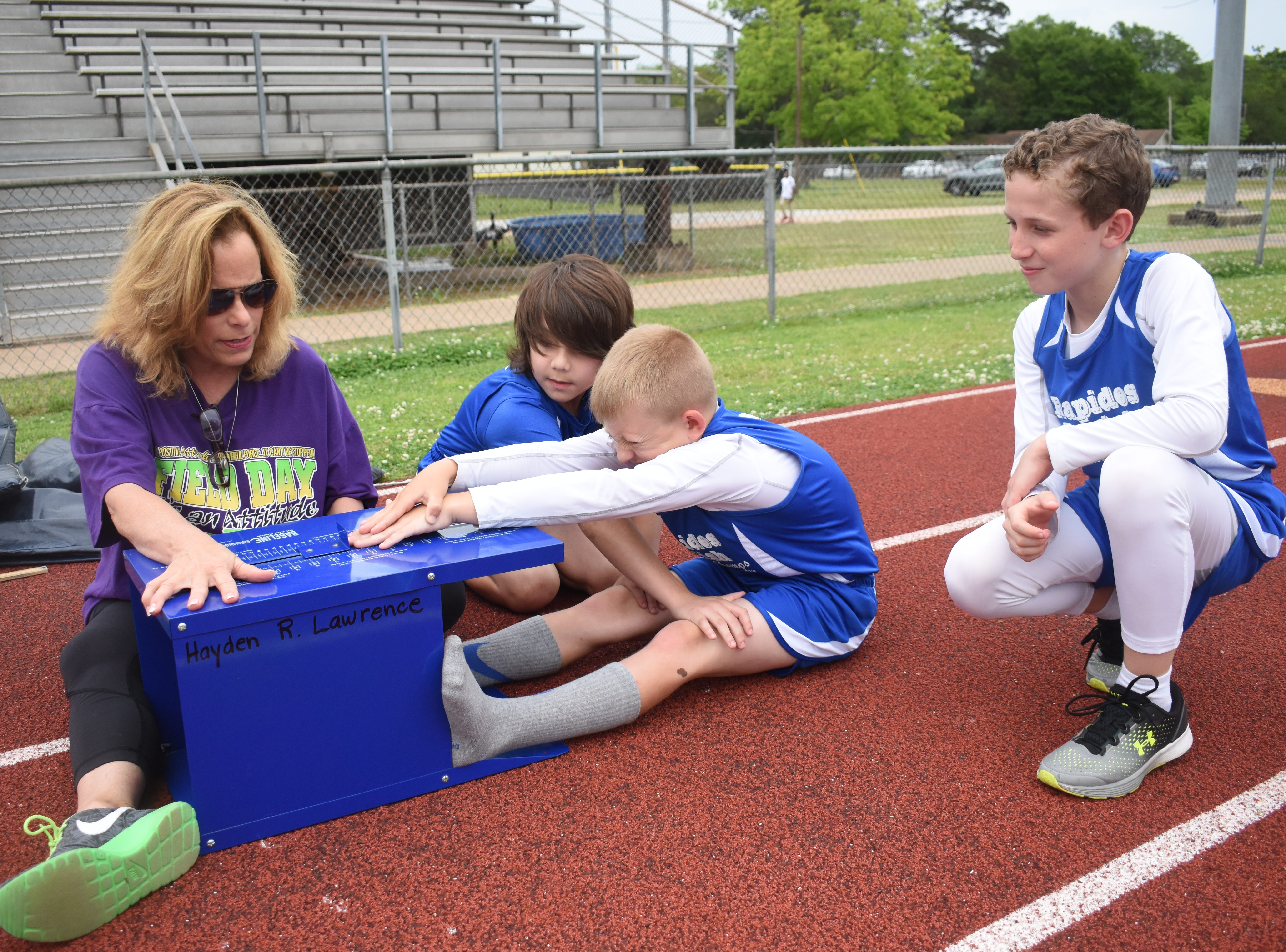 Margaret LaBorde, Rapides Parish Fitness team coach and coordinator (left) watches Jaxon Ross complete a sit and reach. Ross and Jacob Dean (right), both of Nachman Elementary School, and Bryce Warthen (back, second from left) of Hayden Lawrence Elementary School, are part the 2019 Rapides Parish Fitness Team. They and three other Rapides Parish elementary school students will compete in the 2019 State Championship Fitness Meet to be held Saturday, April 27, 2019 at Alexandria Senior High School. The meet is part of the Governor's Council on Fitness and Sports. Students from throughout Louisiana will compete in seven events: 50-yard dash, sit and reach, pull-ups,  shuttle run, curl-ups (sit-ups), standing long jump, and the 600-yard run. For the past three years, the Rapides Parish Fitness Team has placed first at the meet. Dean was the highest scoring boy last year and won the title of 2018 Mr. Fitness for the State of Louisiana. The meet will be from 10 a.m. to 2 p.m.