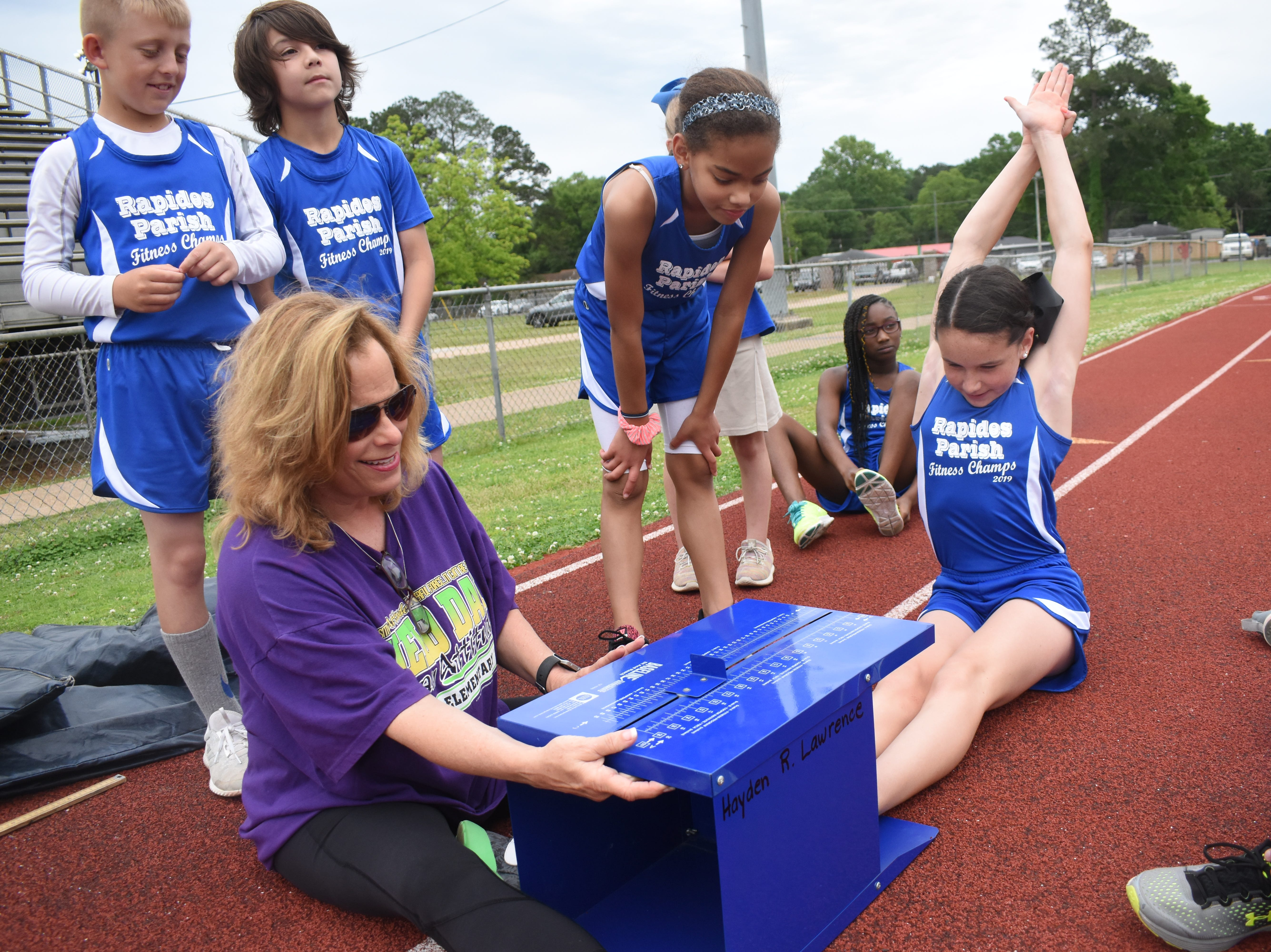 Margaret LaBorde, Rapides Parish Fitness team coach and coordinator (left) watches Aubree Davis of Ball Elementary School complete a sit and reach. Aubree and other five other Rapides Parish elementary school students will compete in the 2019 State Championship Fitness Meet to be held Saturday, April 27, 2019 at Alexandria Senior High School. The meet is part of the Governor's Council on Fitness and Sports. Students from throughout Louisiana will compete in seven events: 50-yard dash, sit and reach, pull-ups,  shuttle run, curl-ups (sit-ups), standing long jump, and the 600-yard run. For the past three years, the Rapides Parish Fitness Team has placed first at the meet. Dean was the highest scoring boy last year and won the title of 2018 Mr. Fitness for the State of Louisiana. The meet will be from 10 a.m. to 2 p.m.