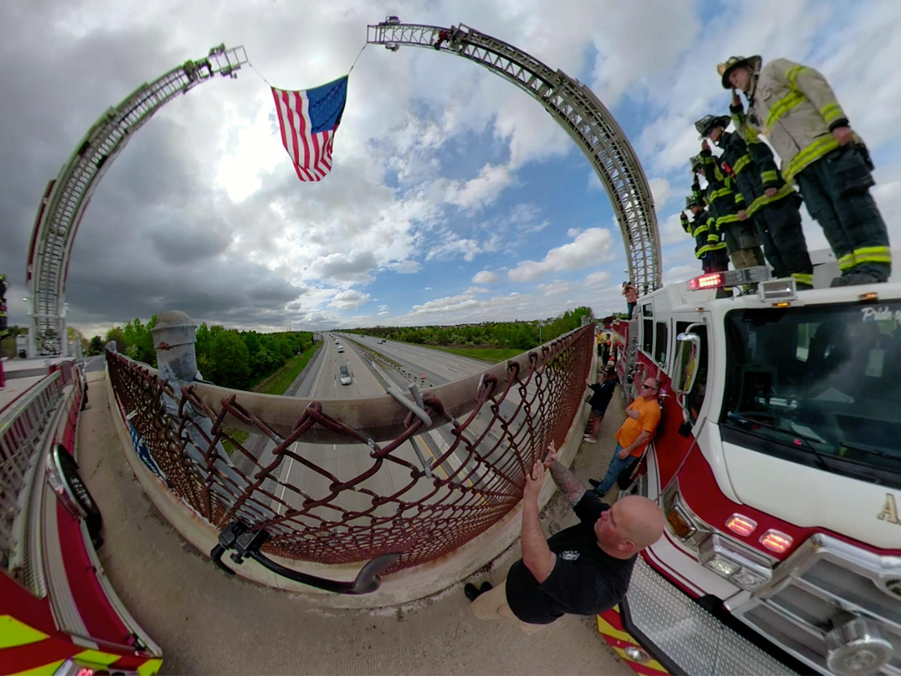 Firefighters salute Marine SSgt Christopher Slutman's funeral procession from the Kirkwood - St. Georges Road overpass above Route 1 in St. George Monday, April 22, 2019.