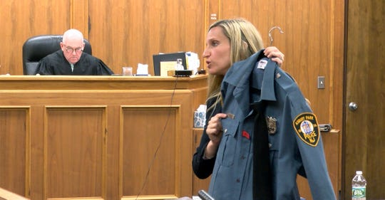 During her opening argument Wednesday, April 24, 2019, Assistant Monmouth County Prosecutor Caitlin Sidley holds Asbury Park police officer Terrance McGhee's shirt.   Dante Allen is charged with attempted murder of the officer.