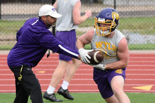 Wylie running back Jackson Smith takes a handoff from assistant coach Grant Martin during the first spring practice at Bulldog Stadium on Wednesday.