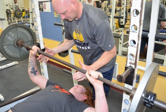 Battle Creek Central football coach Lorin Granger spots Blaise Koeneke during a weight lifting session at BCC as the two prepare for the upcoming All-City Lift-A-Thon.