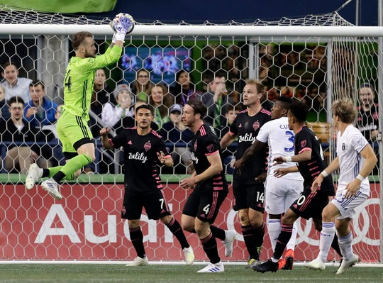 Seattle Sounders goalkeeper Stefan Frei, left, leaps to make a stop against the San Jose Earthquakes during the first half of an MLS soccer match, Wednesday, April 24, 2019, in Seattle.