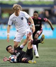 Seattle Sounders midfielder Nicolas Lodeiro, bottom, goes down next to San Jose Earthquakes defender Florian Jungwirth, standing, during the first half of an MLS soccer match, Wednesday, April 24, 2019, in Seattle.