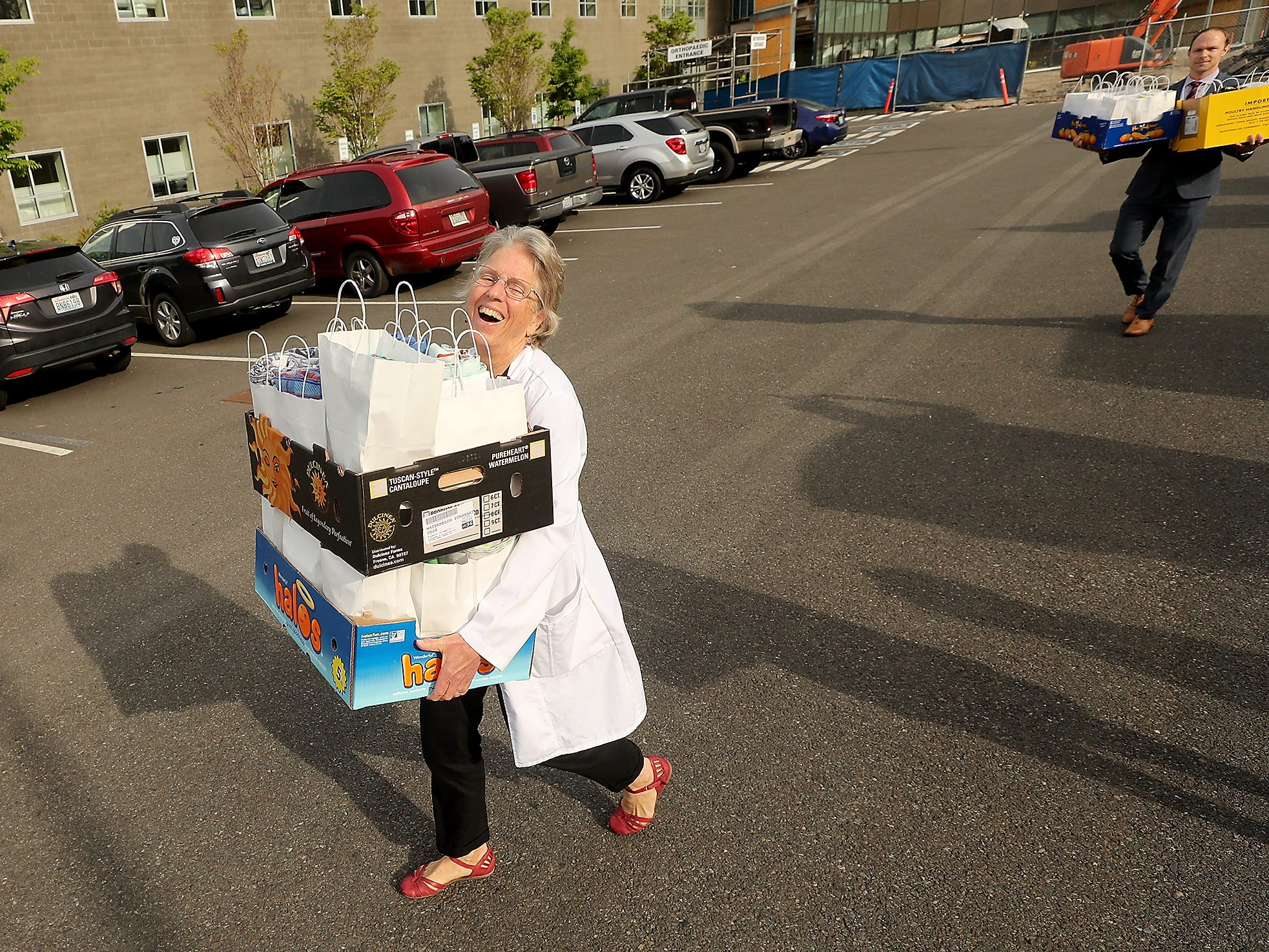 Clinical Nurse Specialist, RN Peggy Visher laughs as she carries boxes filled with bags of handmade blankets from the parking lot into Harrison Medical Center in Silverdale on Thursday, April 25, 2019.