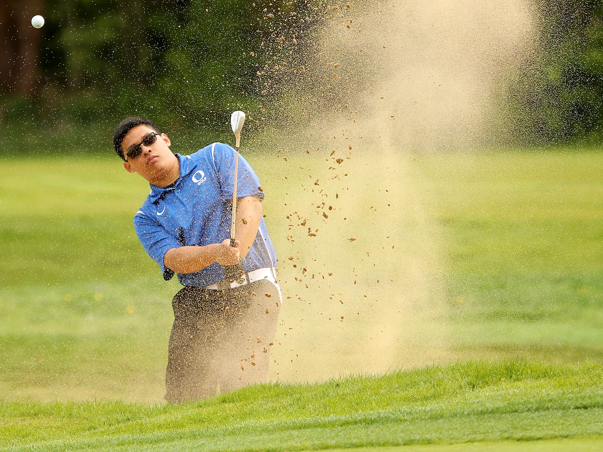 The sand flies as Olympic's Adrian Basaliza hits a shot out of a bunker during the Tim Higgins Memorial Golf Tournament at the Kitsap Golf & Country Club in Bremerton on Thursday, April 25, 2019.