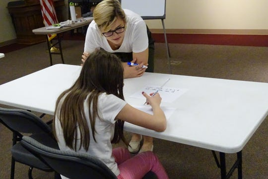 Erin Rhoades, circulation manager of the Bucyrus Public Library, helps 11-year-old Jasmine Taylor learn cursive handwriting on Wednesday afternoon in the library.
