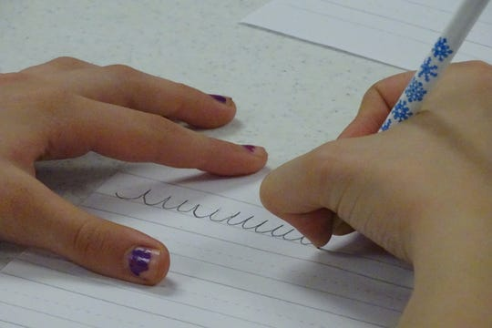 Jasmine Taylor practices a basic component of cursive handwriting during a class on Wednesday afternoon in the library.