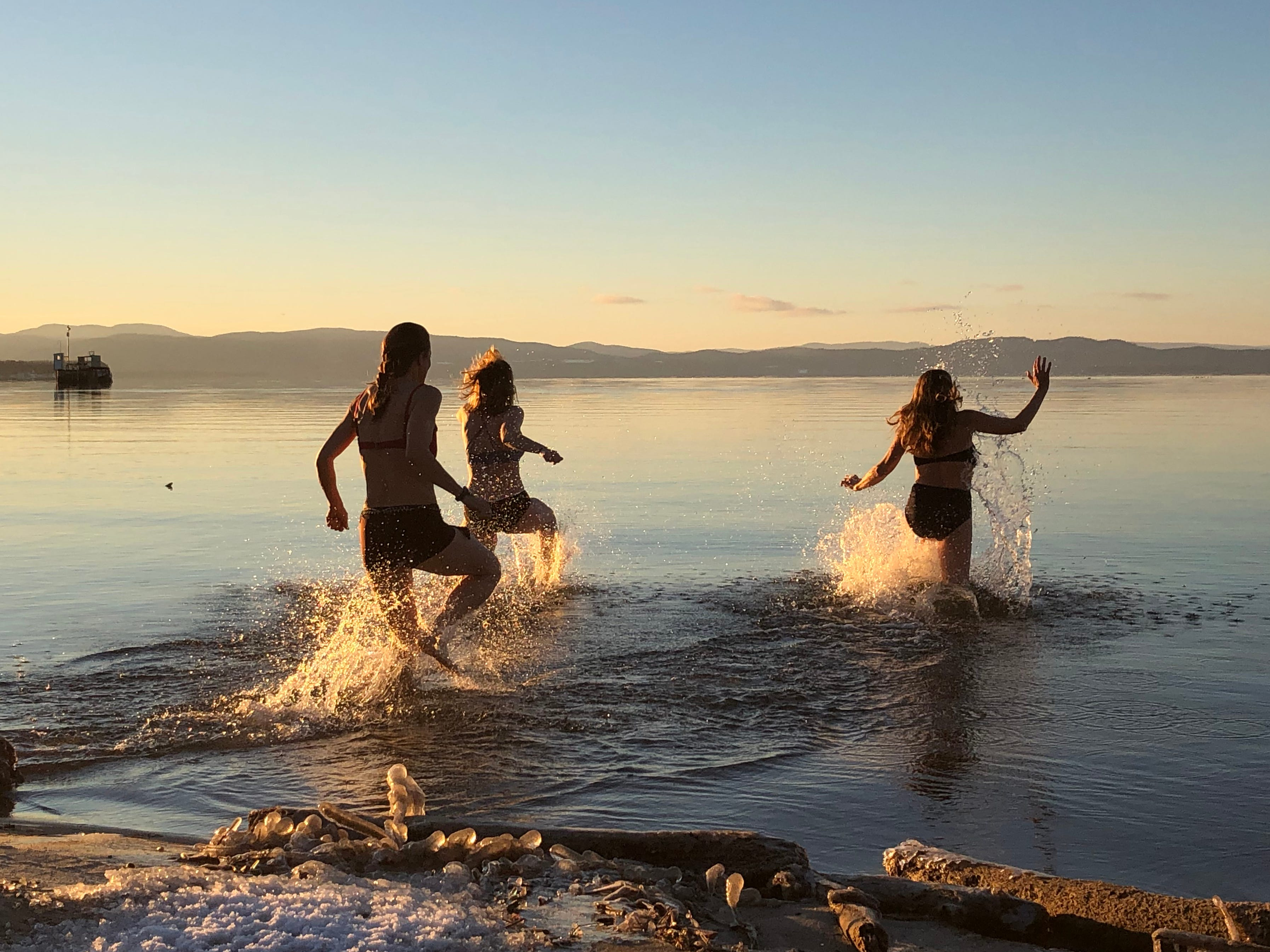 """Katharine Montstream of Burlington (at right) dashes into Lake Champlain for a quick dip with her daughter, Charlotte Dworshak (center), and sister, Sydney Montstream-Quas, on Dec. 25, 2018. Neither of Montstream's companions wanted to join her into the 38-degree water (and 22-degree air), she said, """"But, since it was my birthday, they felt like they had to."""""""