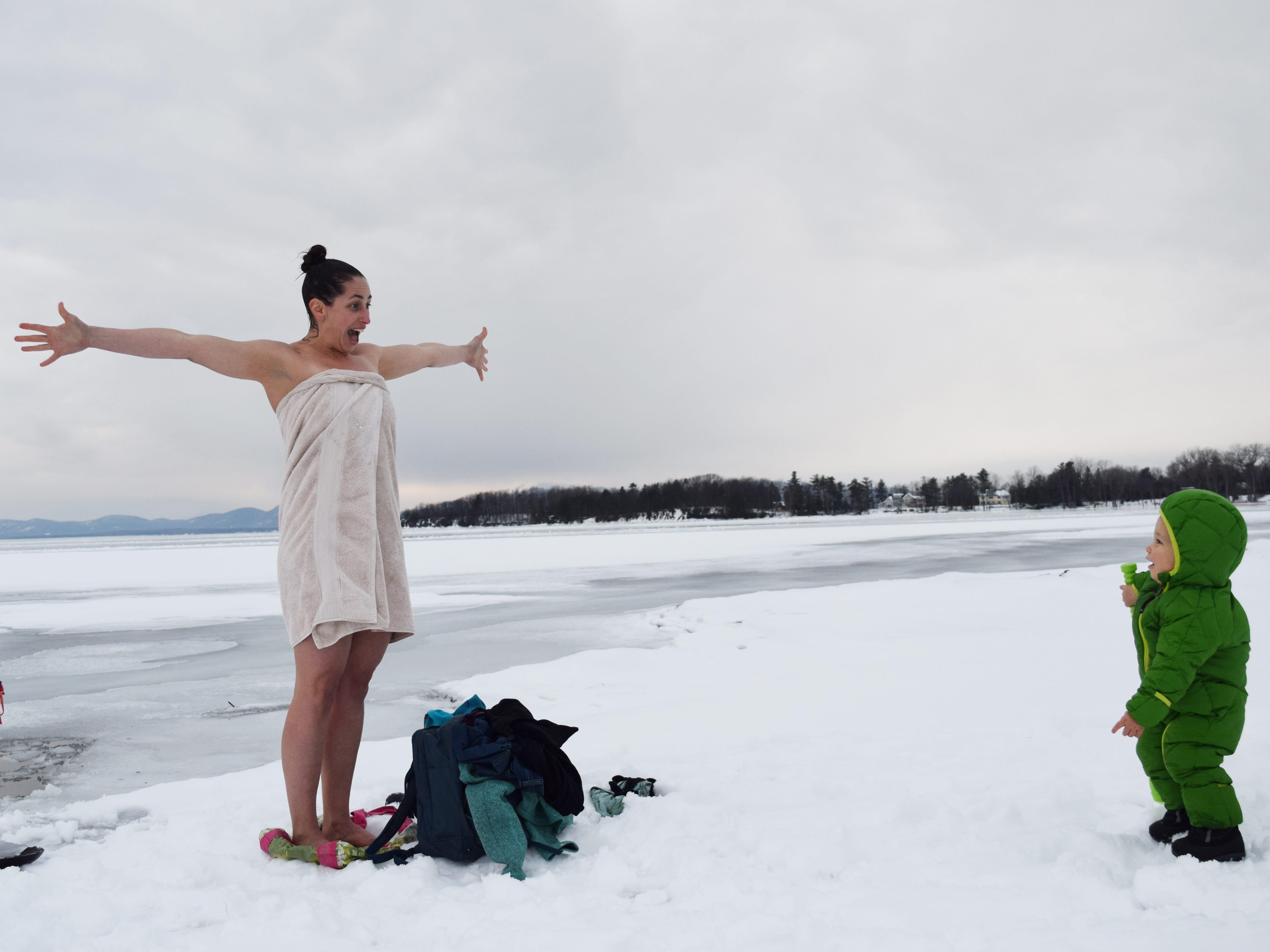 Elise Schadler of Burlington greets her son, Finn, after taking a quick dip in Lake Champlain on Feb. 15, 2019.