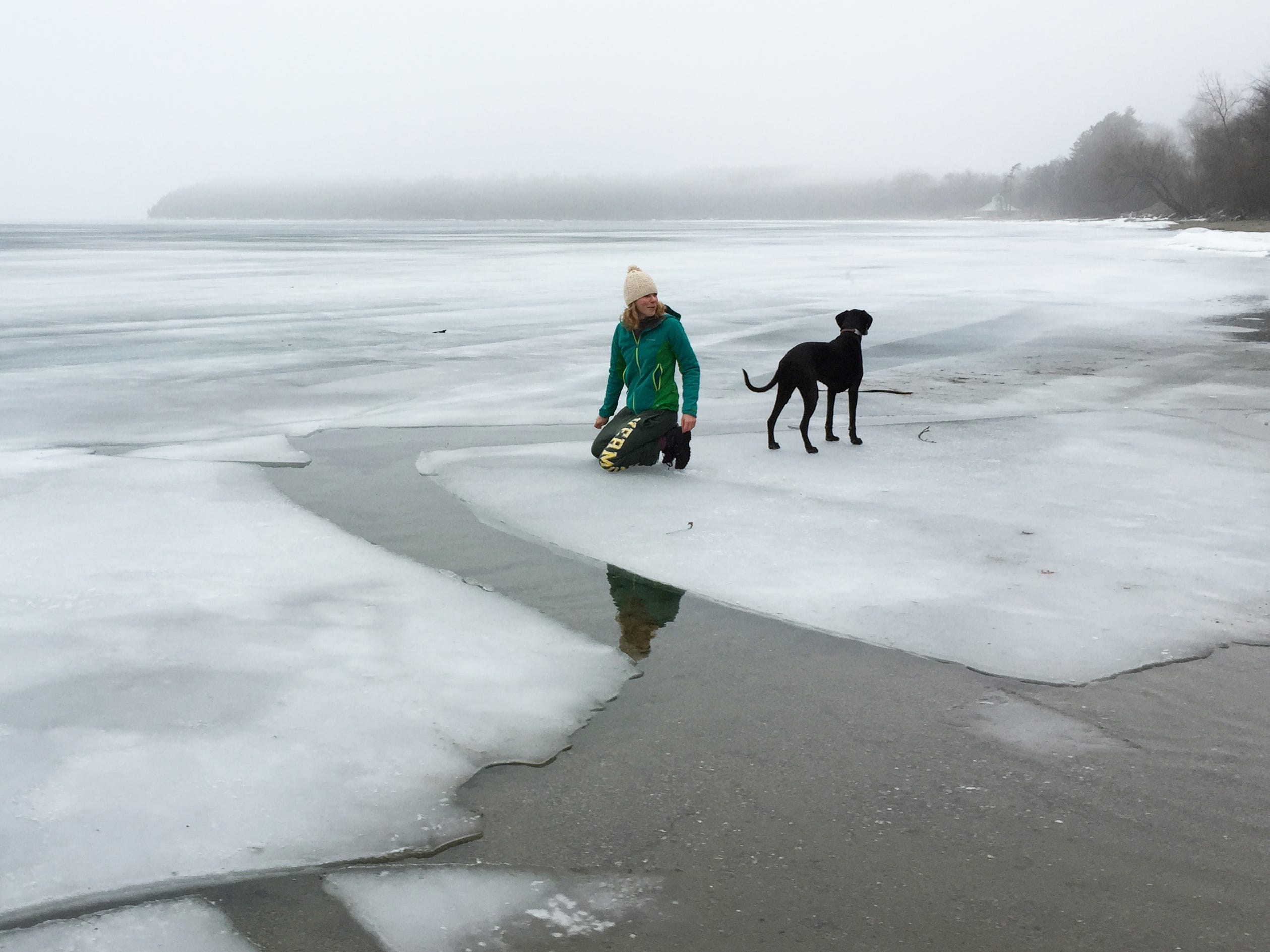 Monika XXX and Luna, the dog, explore ice formations on the Burlington shoreline, looking for an ideal spot to swim on March 27, 2015.