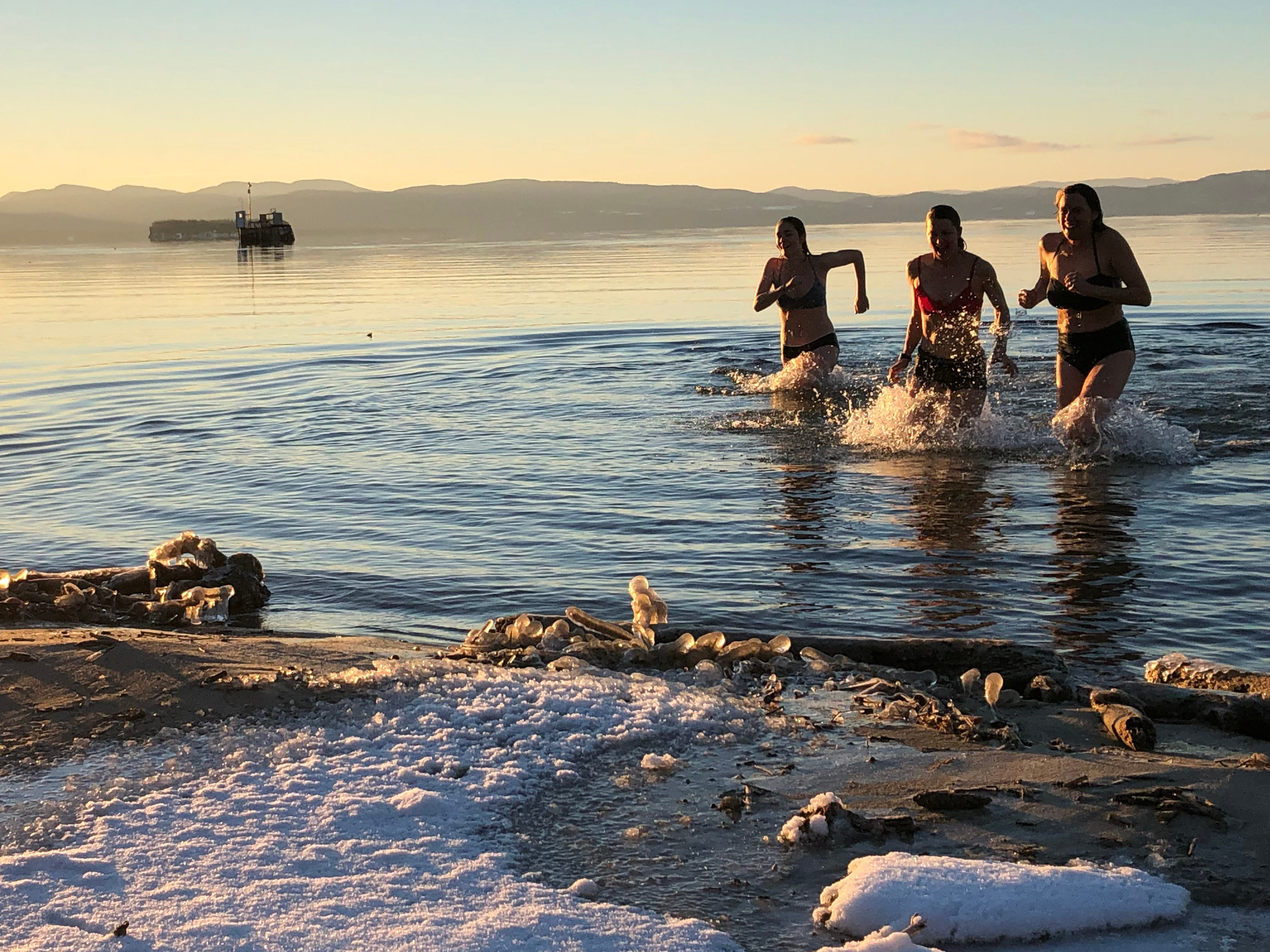 Katharine Montstream of Burlington (at right) dashes back to Oakledge beach after a quick dip with her sister, Sydney Montstream-Quas (center) and daughter, Charlotte Dworshak, on Dec. 25, 2018.