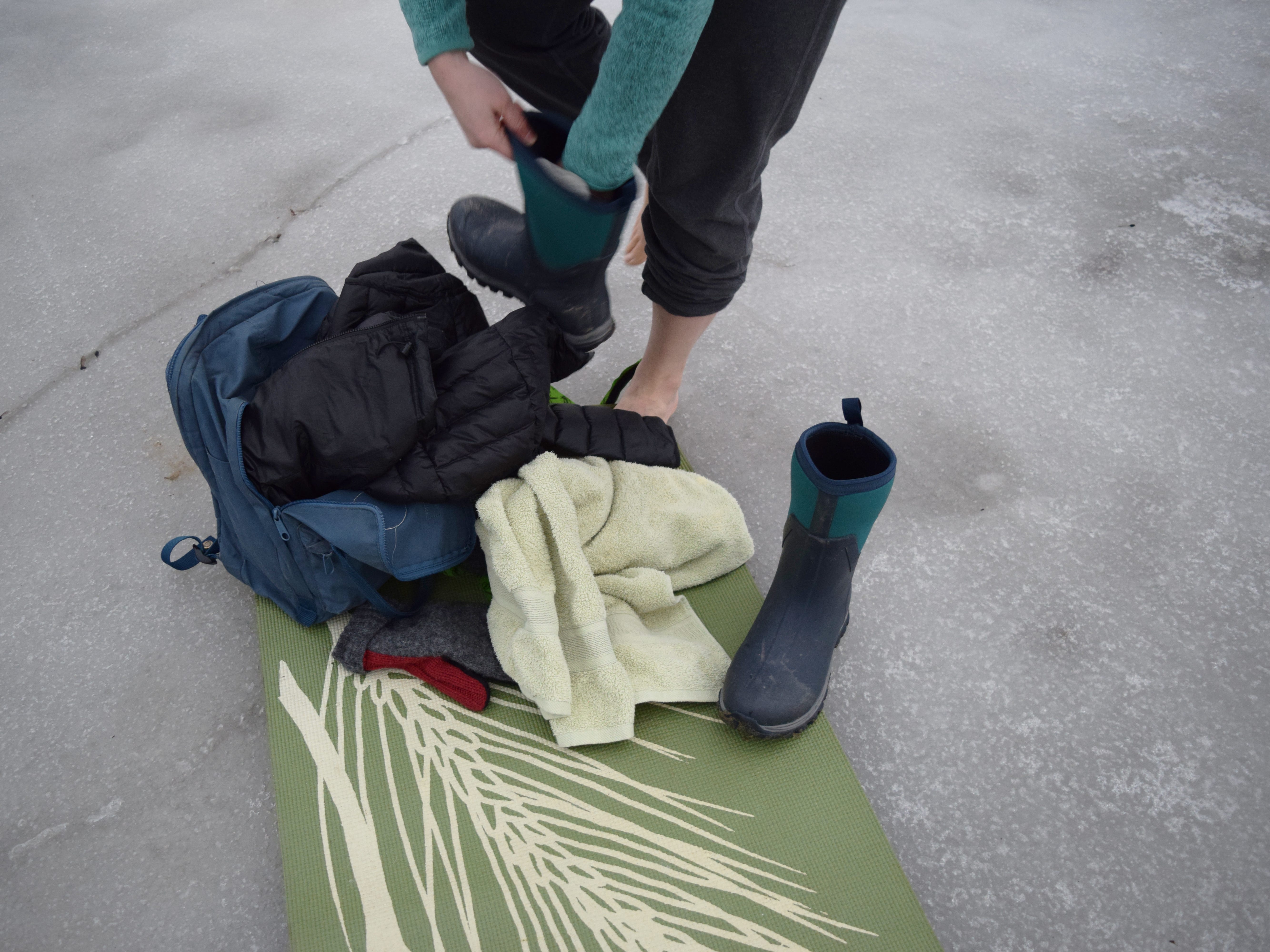 Elise Schadler of Burlington scoots into warm boots after having fully immersed herself in Lake Champlain on Feb. 21, 2018.