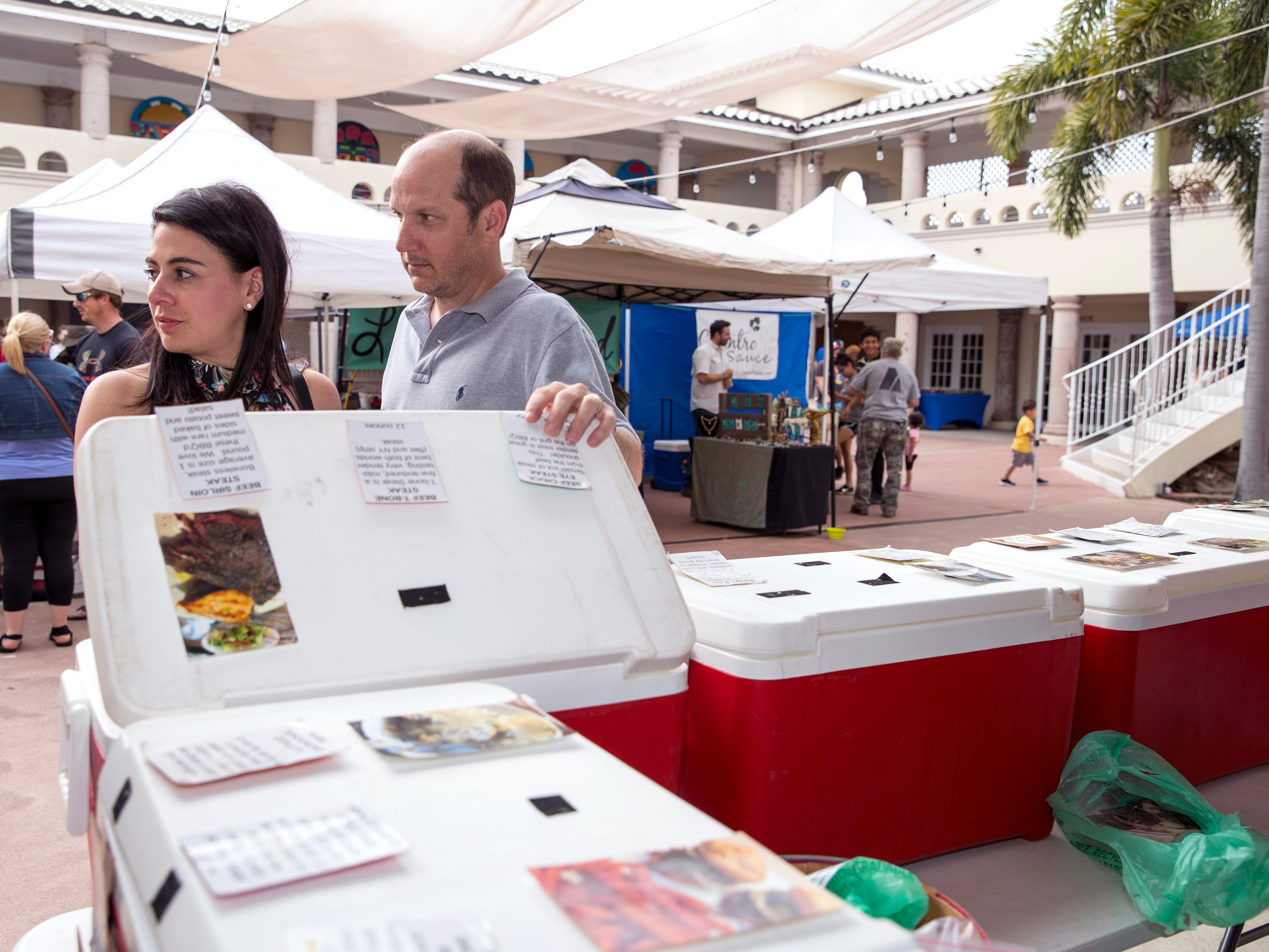 Margie Durst and her husband, Robby Durst, shop for grass-fed meat at Turkey Hollow Farm  at the Corpus Christi Downtown Farmers Market on Wednesday, April 24, 2019. It offers a variety of seasonal produce, grass fed beef, pastured raised poultry, prepared goods such as roasted coffee, sweets and preserves and baked goods. It is open weekly on Wednesday from 5 to 8 pm at 100 N. Shoreline Blvd.