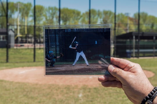 Jeff Fante holds up an image of his son Dane Fante at bat on the Moorestown baseball field Wednesday, April 24, 2019. Dane Fante, a 2016 Moorestown graduate, died in a car accident in February, 2018. The field will be renamed in his honor on May 10.