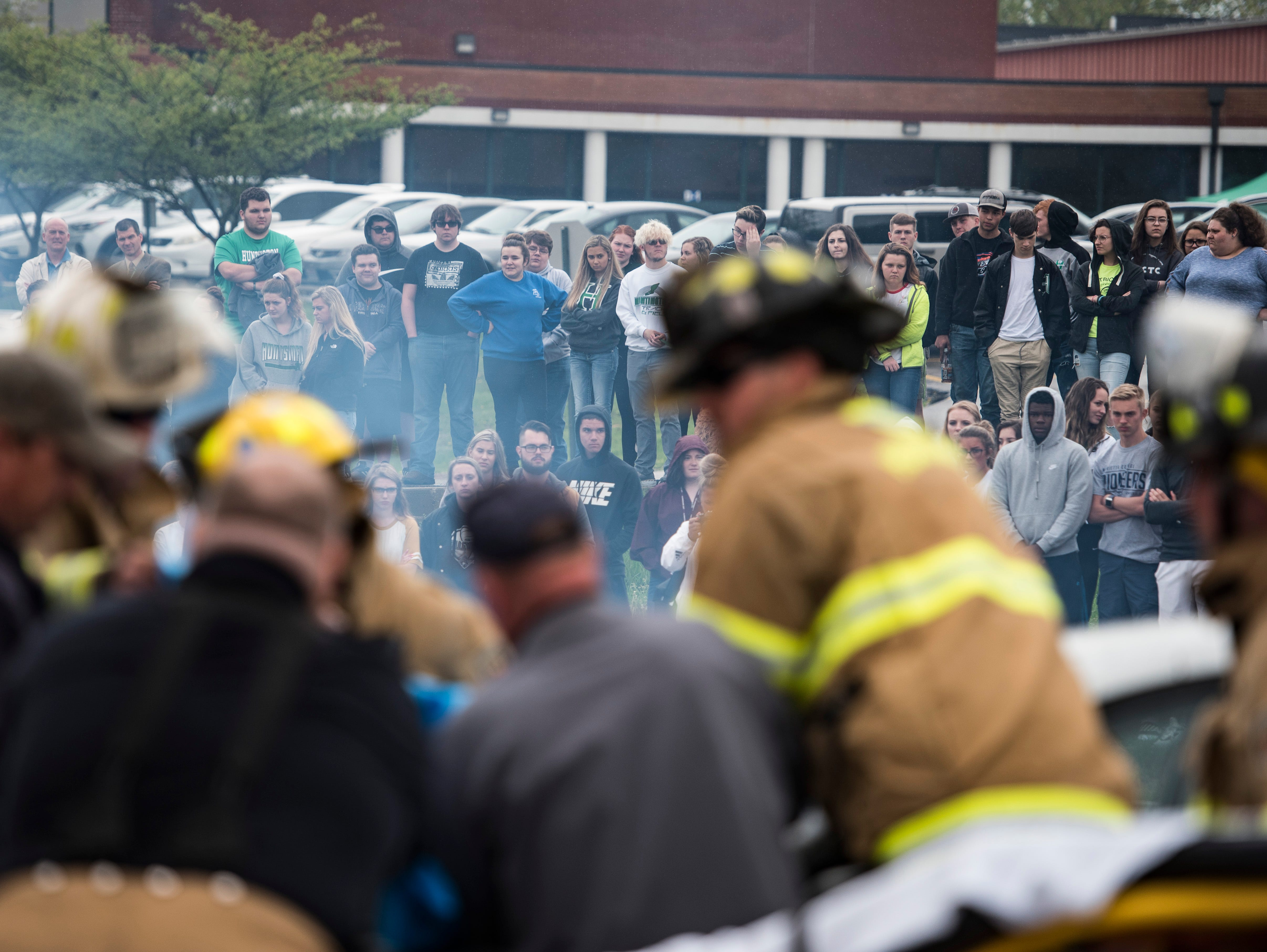 """Huntington students watch as firefighters and paramedics try to free bodies from a vehicular mock crash in Huntington Township on Thursday, April 25, 2019.  """"The purpose is to help deter students from drinking and driving during the prom season, """"said Detective Bud Lytle. """"Throughout history we have had an increase number of accidents involving teenagers during the season and want to show them this can be a result."""""""