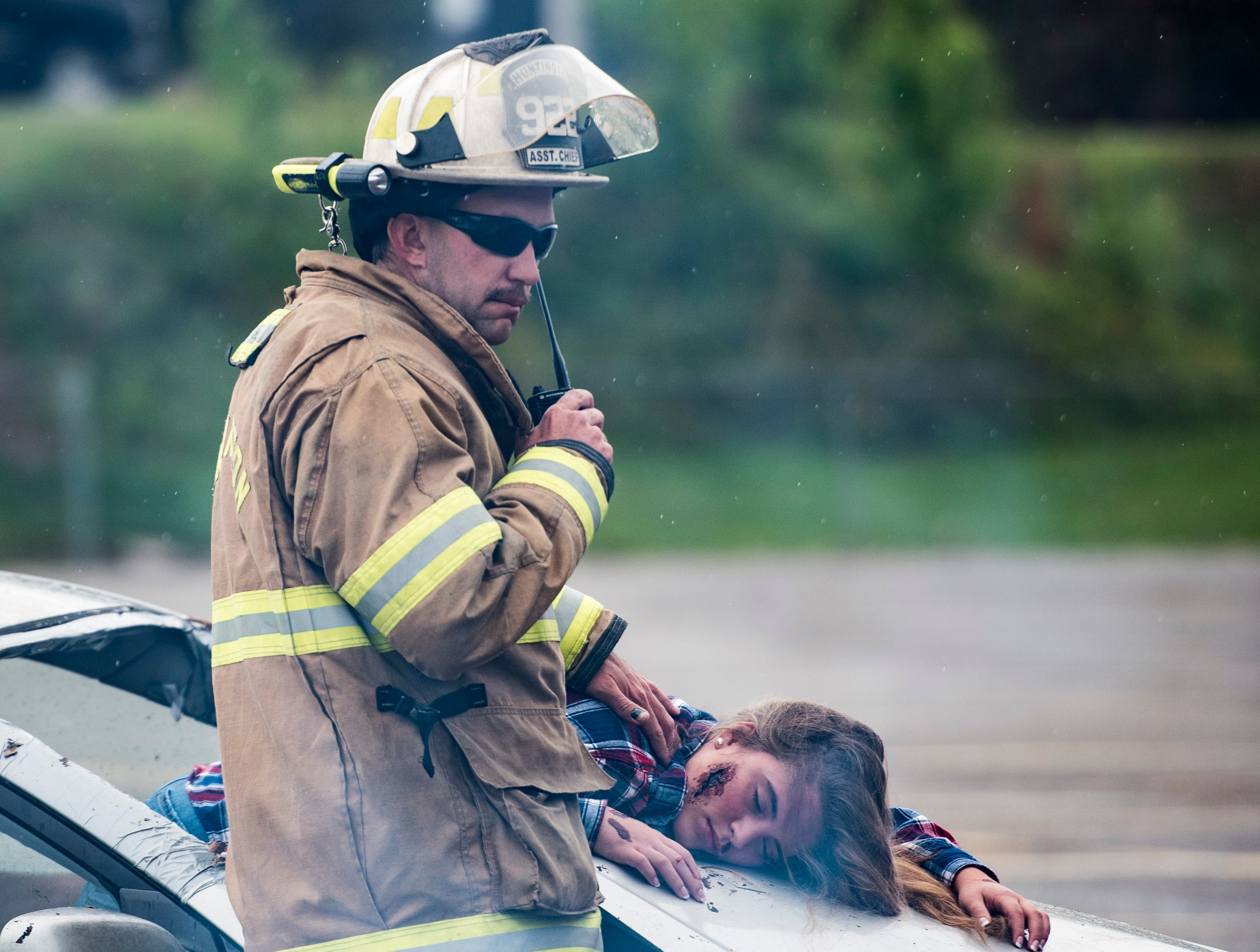A Huntington firefighter calls in a dead body during a vehicular mock crash in Huntington Township on Thursday, April 25, 2019.