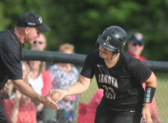 Lakota East catcher Mackenzie Rieck gets congratulations from her coach Steve Castner after  hitting a home run, during the Thunderhawks regionals semi-final against Lakota West, Thursday, May 26,2016. (Photo by Tony Tribble)