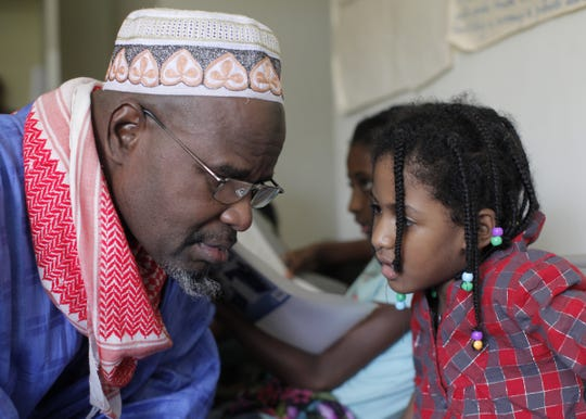 A young girl, Aissata Diallo, recites a paper to her elder, Oumar Dia, in the Lockland apartment complex where children spend a few hours each Saturday and Sunday studying Pulaar language and Fulani culture.
