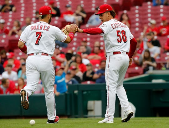 Cincinnati Reds third baseman Eugenio Suarez (7) and starting pitcher Luis Castillo (58) high five after the top of the first inning of the MLB National League game between the Cincinnati Reds and the Atlanta Braves at Great American Ball Park in downtown Cincinnati on Thursday, April 25, 2019.