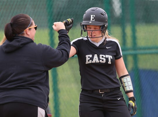 Lakota East player Abigail Niehaus (No. 5) celebrates with her third-base coach during the Thunderhawks' softball game against Hamilton, Wednesday, April 24, 2019.