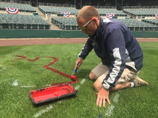 Head groundskeeper Dan Purner paints the Patriots logo in preparation for Opening Day.