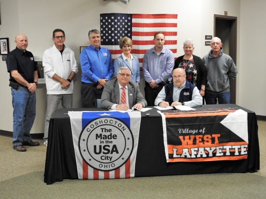 Mayor Steve Mercer of Coshocton and Mayor Stephen Bordenkircher of West Lafayette in March signed a contract for water and water service from the city to the village at Coshocton City Hall. Standing are Utilities Director Dave McVay, Councilman Roger Moore, Safety Services Director Max Crown, City Auditor Sherry Kirkpatrick and West Lafayette council members Craig Bordenkircher, Christie Maurer and Ron Lusk.