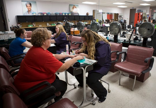 Mallory Arlinhalt, a junior at the Coshocton County Career Center, gives Coshocton resident Becky Mobley a manicure during the Career Center's recent open house.