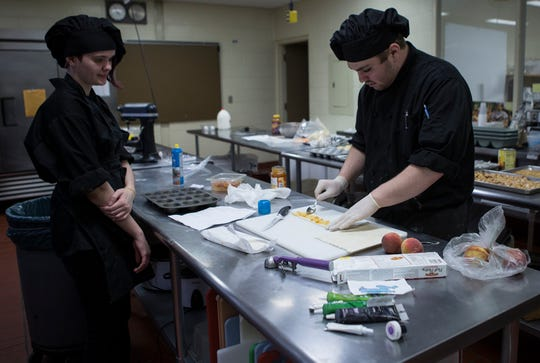 Joshua Meyers, a senior at the Coshocton County Career Center, prepares a pastry while fellow classmate, Aries Shephard watches during the Career Center's recent open house.