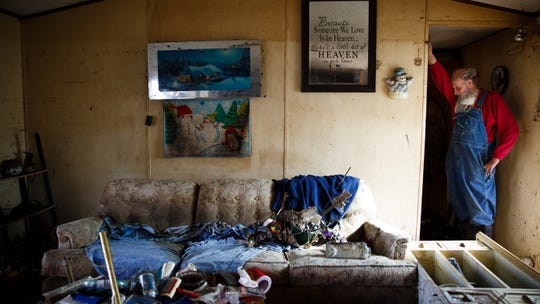 Danny Manchester, 69, hangs his head on his arm as he stands in what was the living room of the trailer he and his wife Mary lived in since 1993 on Tuesday, April 16, 2019, in Pacific Junction. The flooding along the Missouri river in late March broke levees and inundated towns like Pacific Junction with water up to the rafters of homes for weeks. The couple said they weren't sure if they were going to rebuild there or not since they would have to start from scratch again.