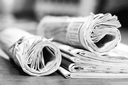 Rolled newspapers and magazines on table.