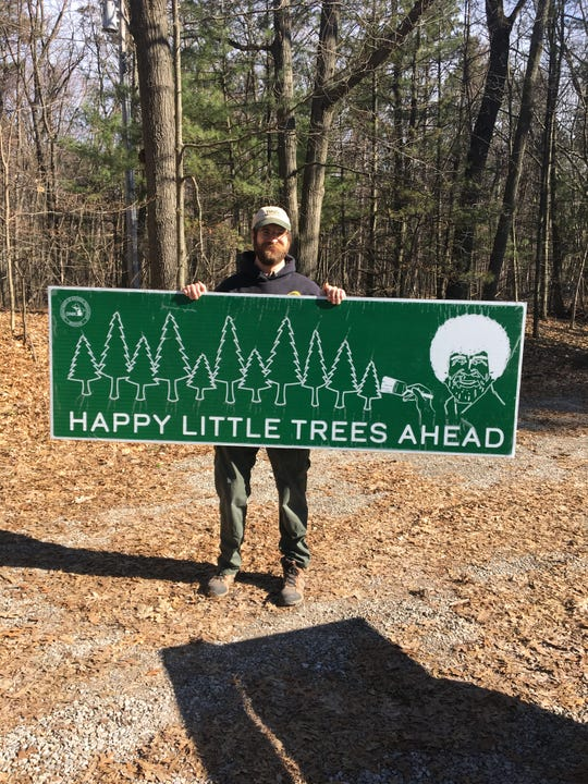 Port Crescent State Park supervisor Brian Dunn holds a new sign to be placed in the park. The sign, featuring Bob Ross, is part of a partnership between the Department of Natural Resources and Bob Ross Inc.