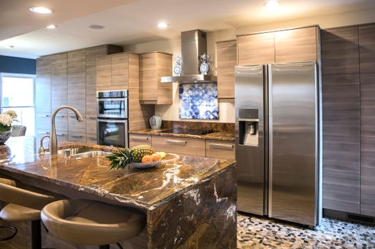 "An all-new kitchen has stainless steel appliances and extensive  ""smart"" storage to keep small appliances and tools put away. The  granite eating bar is in space that used to be a wall. The mixed stone flooring was picked to compliment the multi-hued granite. This co-op was photographed in Detroit, Mich., Tuesday, April, 23, 2019."