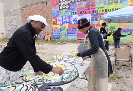 From left, Chazz Miller, community artist for Live6, and Melinda Anderson of Detroit paint wooden butterflies that will be hung on abandoned houses, buildings and lots in the neighborhood, at Live6 Alliance's new Neighborhood HomeBase.