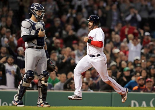 Boston Red Sox's J.D. Martinez, right, scores on a single by Rafael Devers in the second inning.